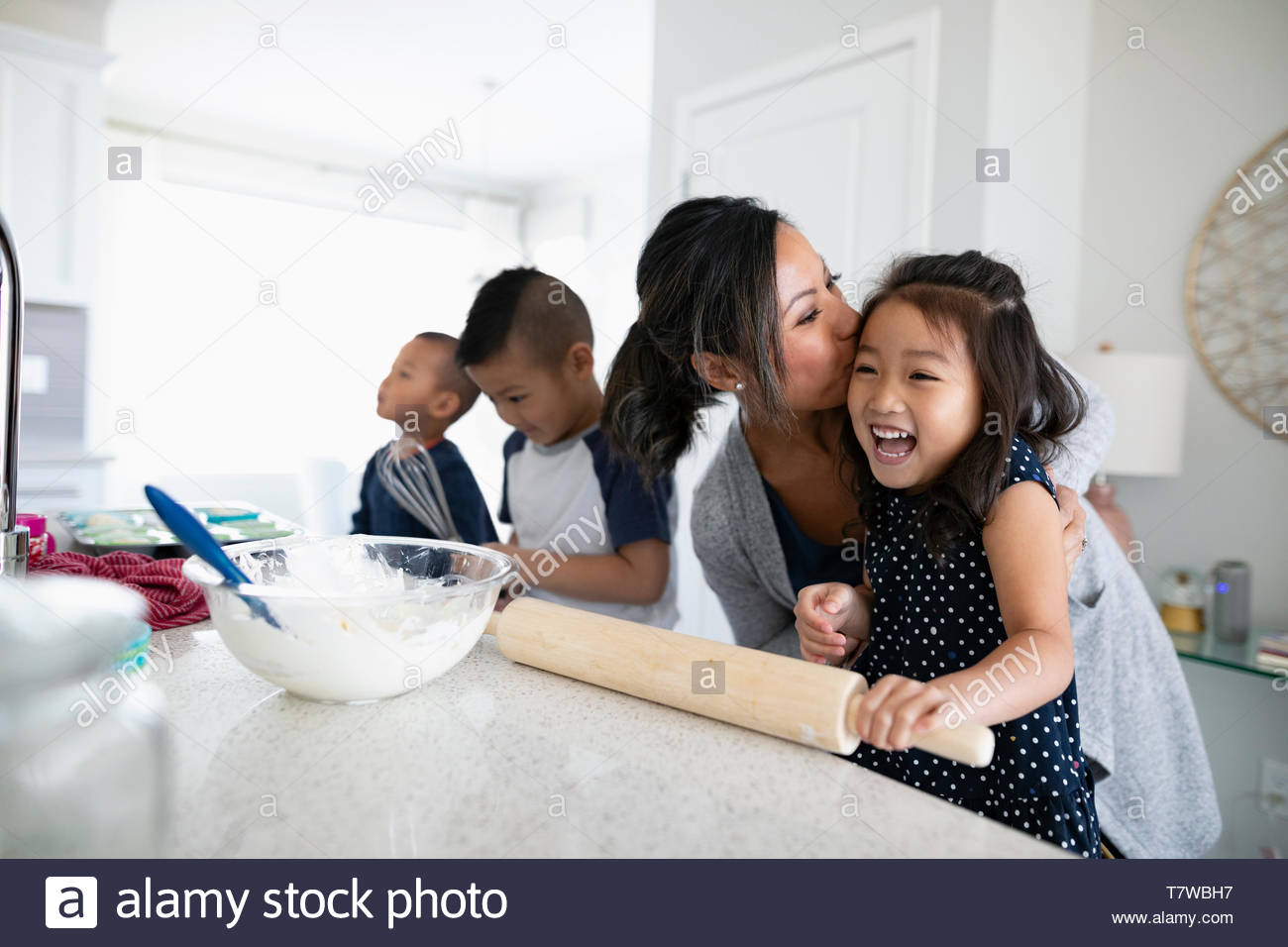 Affectionate mother and children baking in kitchen - Stock Image