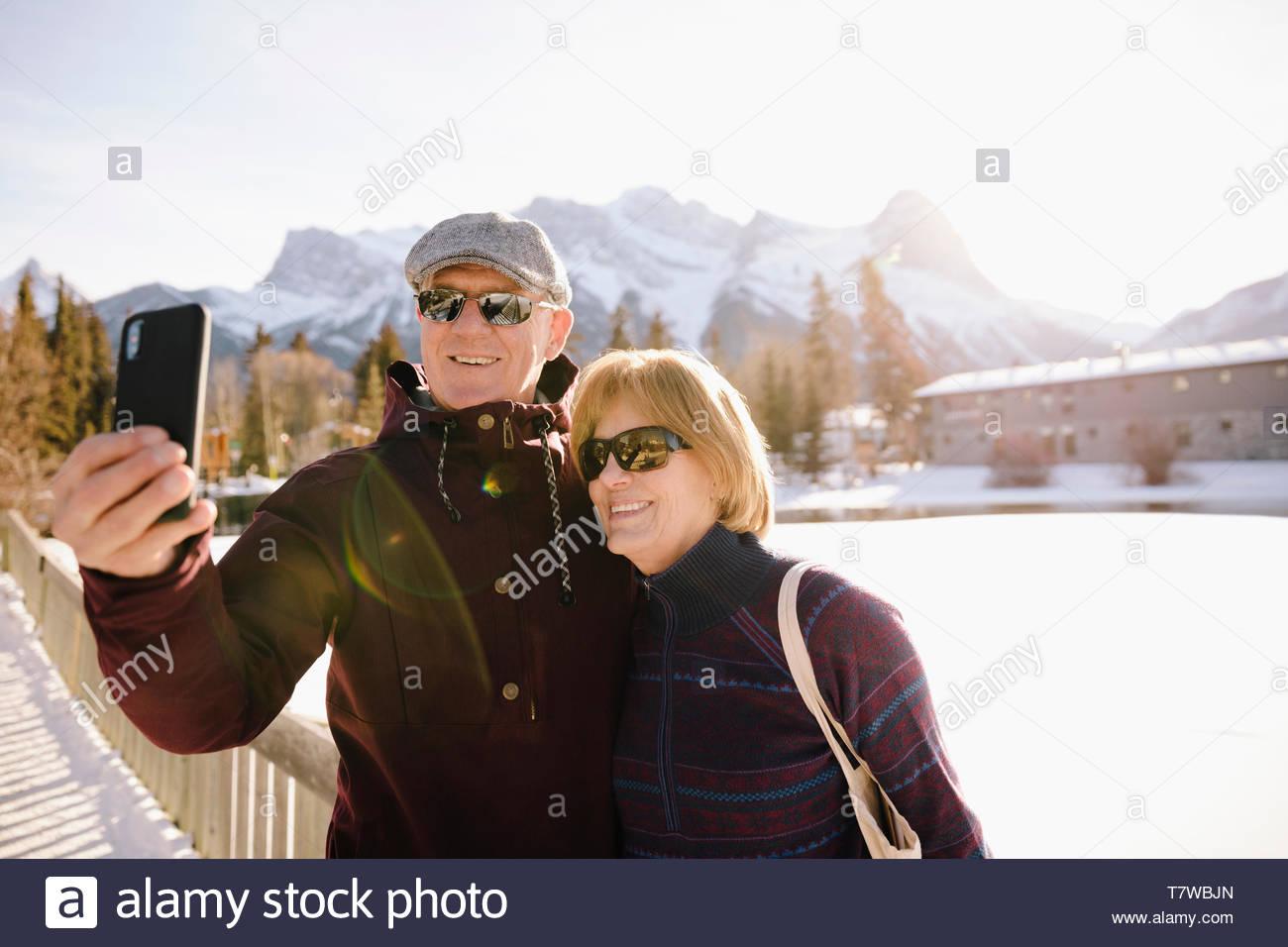 Smiling senior couple taking selfie on frozen pond Stock Photo