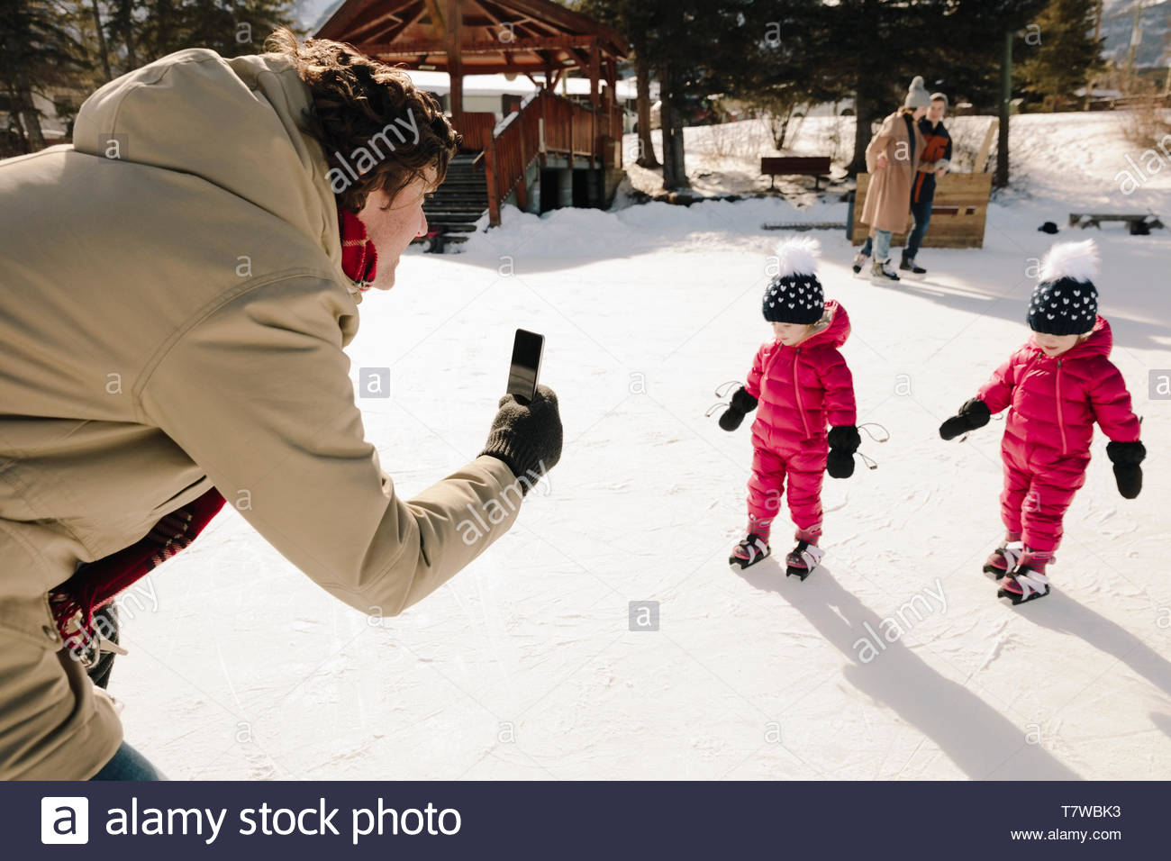 Father with camera phone filming toddler twin daughters ice skating on frozen pond - Stock Image