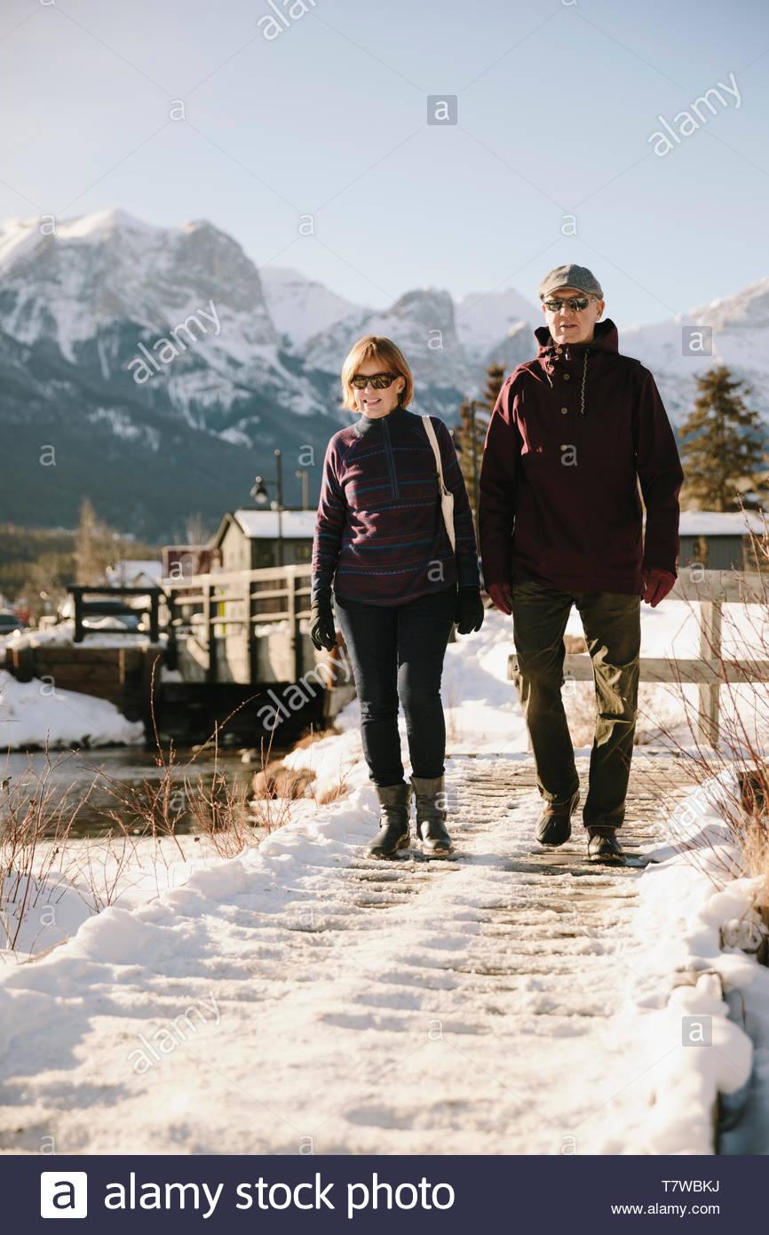 Senior couple walking along snowy path below mountains - Stock Image