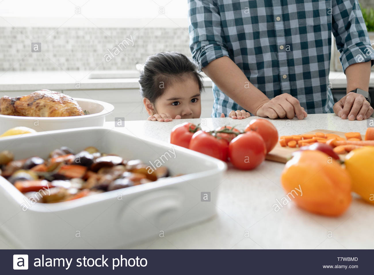 Daughter helping father cook in kitchen - Stock Image