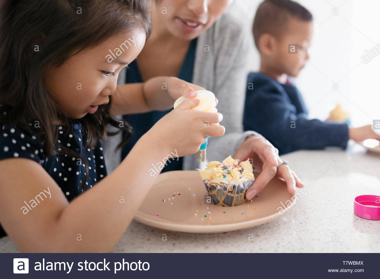 Mother and daughter decorating cupcakes in kitchen - Stock Image