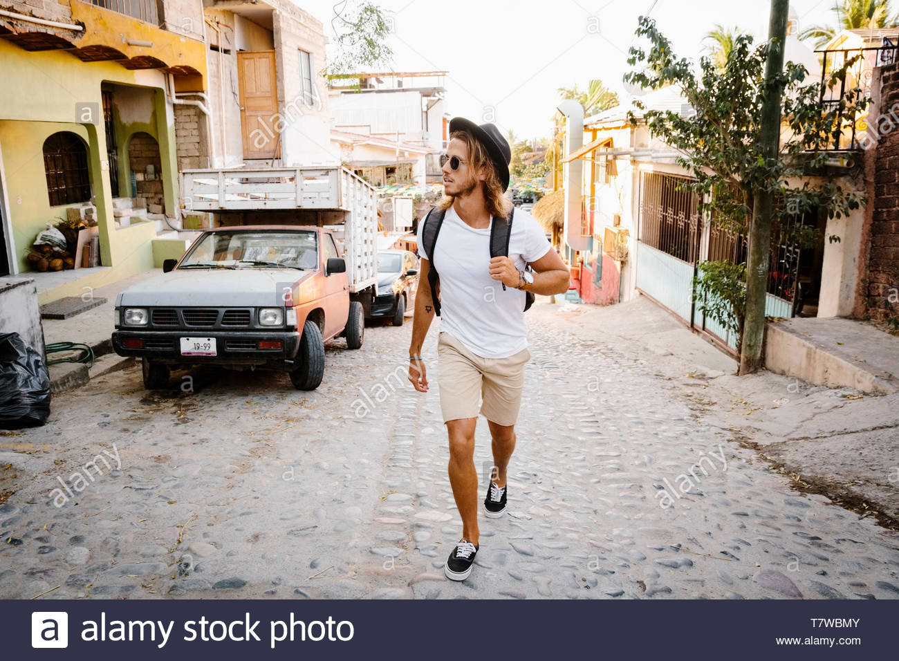 Young male tourist walking on cobblestone street, Mexico - Stock Image