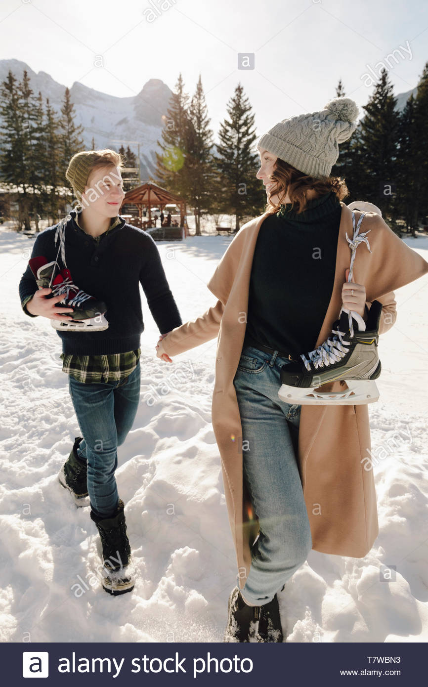 Young couple with ice skates holding hands, walking in snow - Stock Image