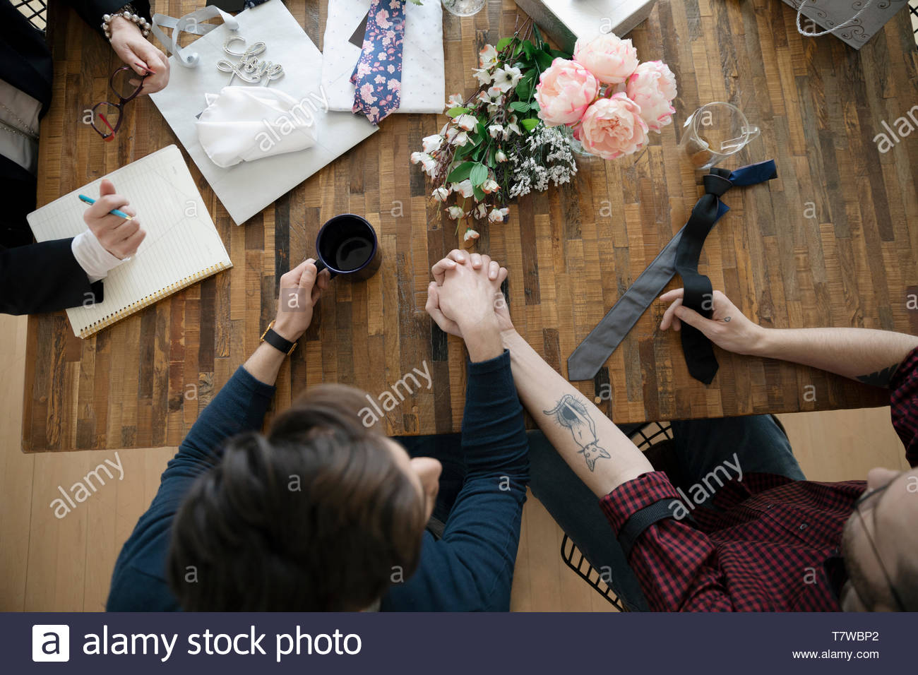 View form above gay male couple holding hands, meeting with wedding planner - Stock Image