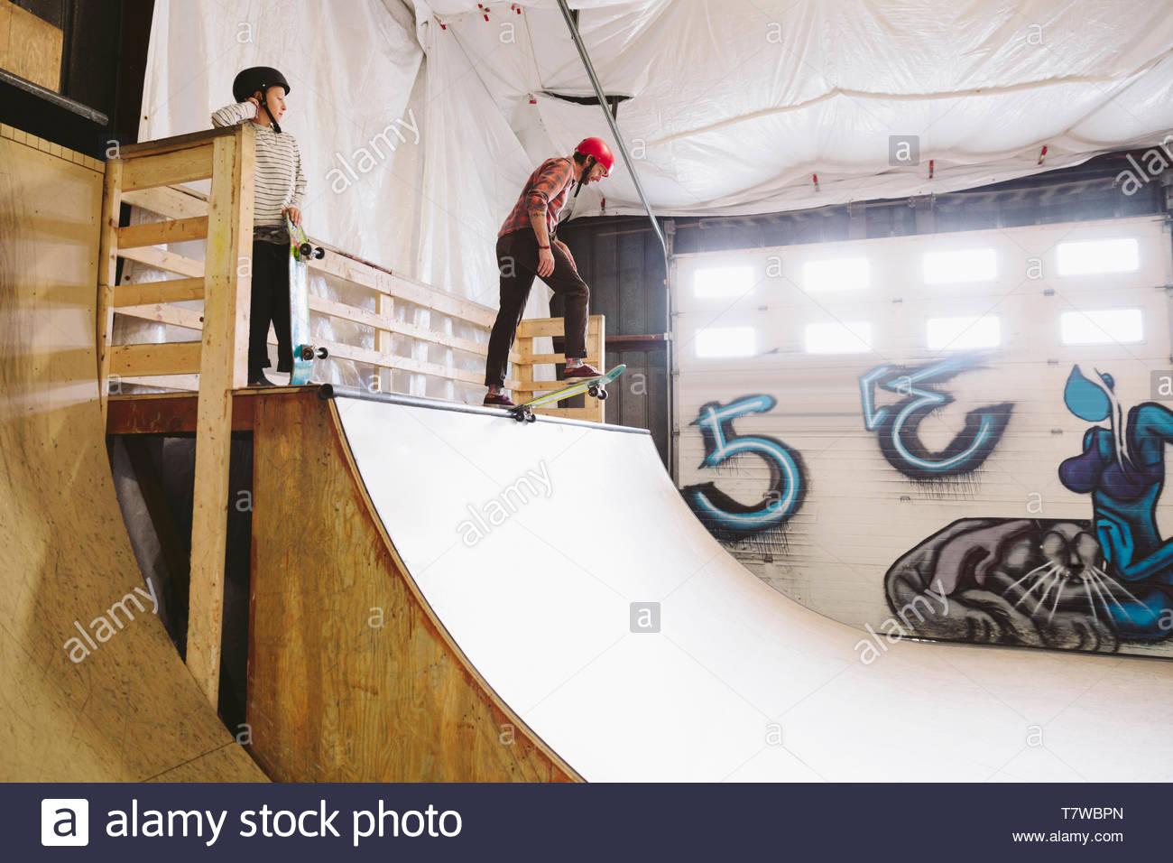 Mature man skateboarding at top of ramp at indoor skate park - Stock Image
