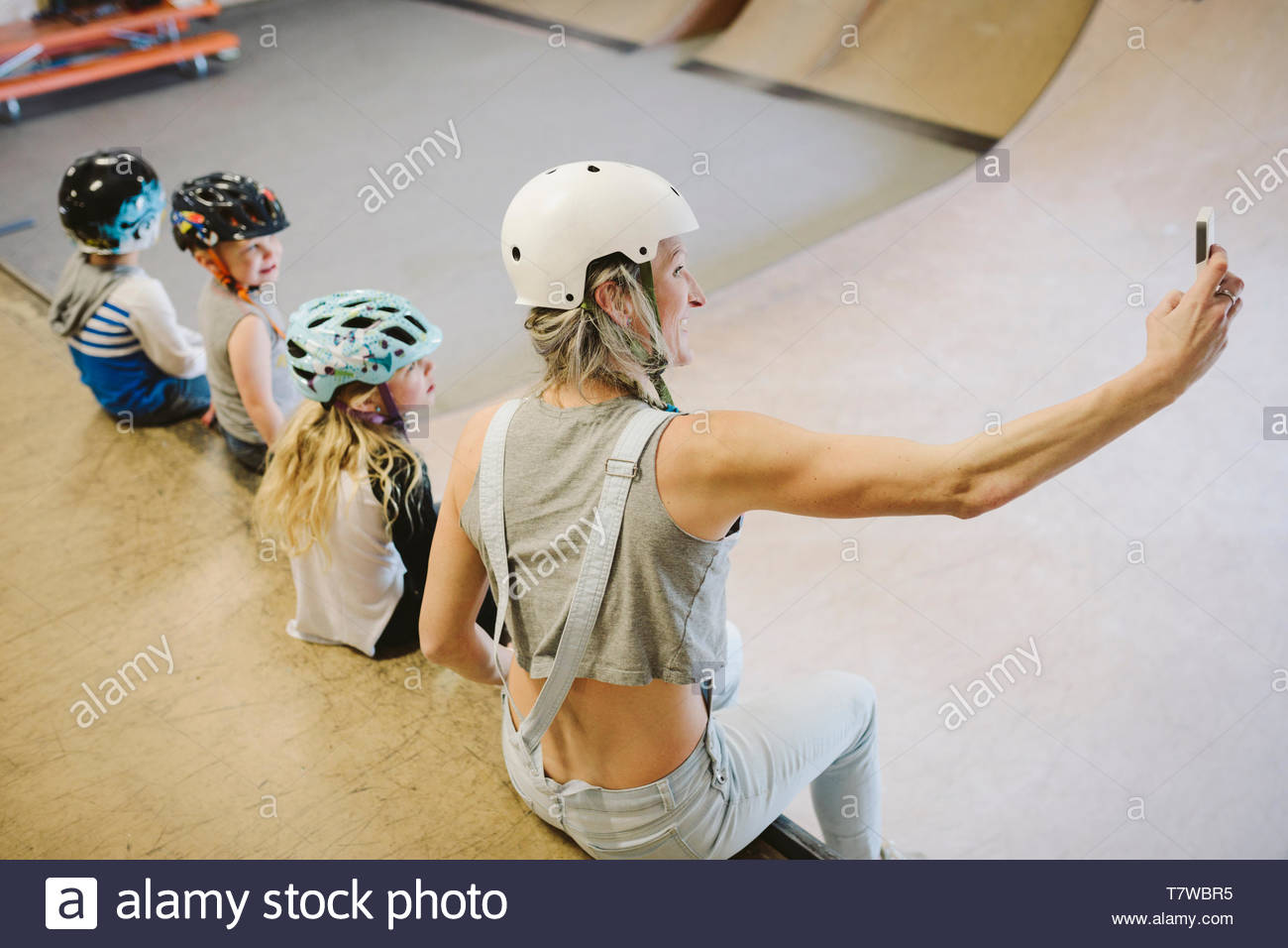 Mother and children taking selfie on ramp at indoor skate park - Stock Image