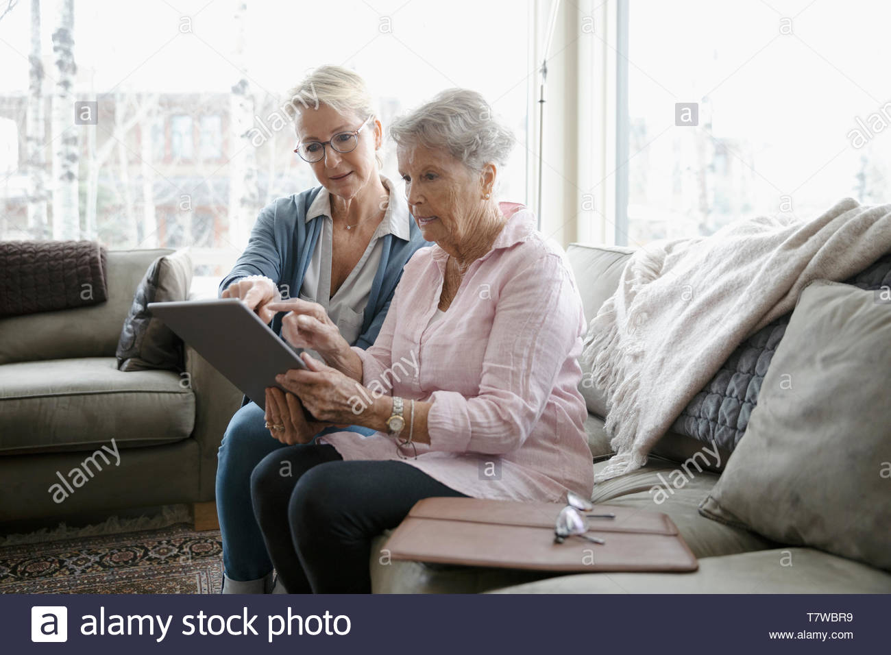 Daughter helping senior mother using digital tablet - Stock Image
