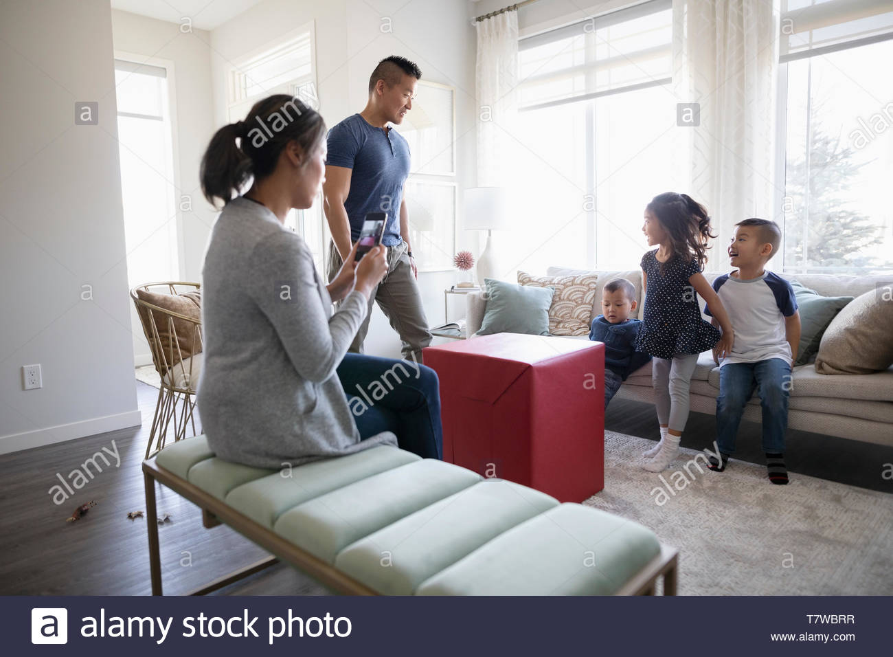 Excited children waiting to open large gift - Stock Image