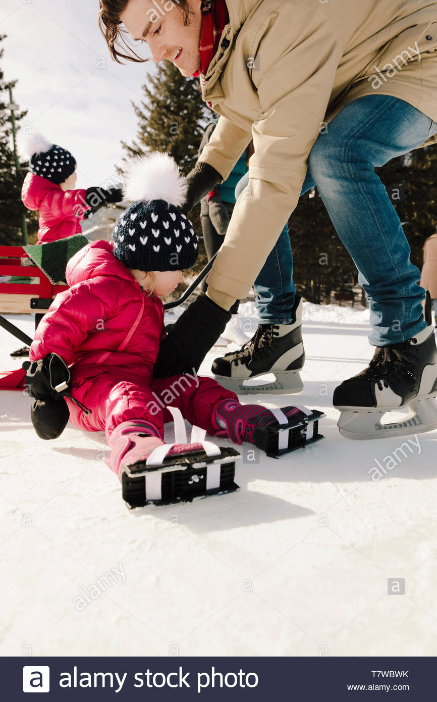 Father helping toddler daughter ice skating - Stock Image