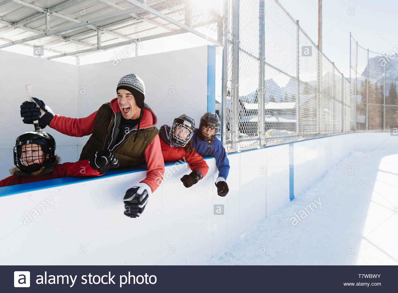 Happy family cheering, watching outdoor ice hockey from sideline bench - Stock Image
