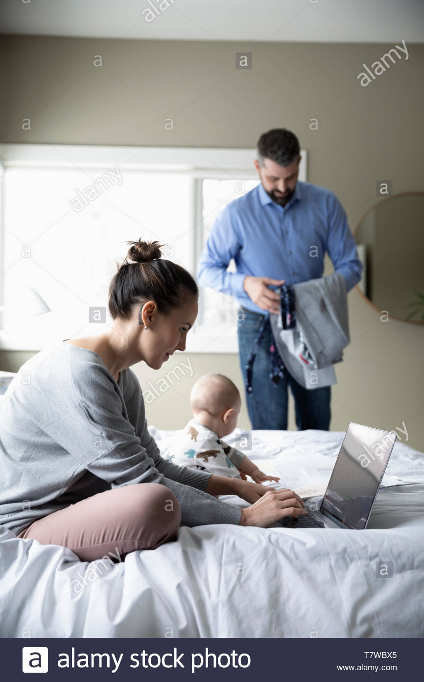 Parents with baby working from home and getting ready for work in bedroom - Stock Image