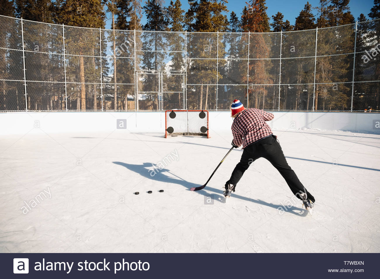 Man playing outdoor ice hockey, practicing penalty shots - Stock Image