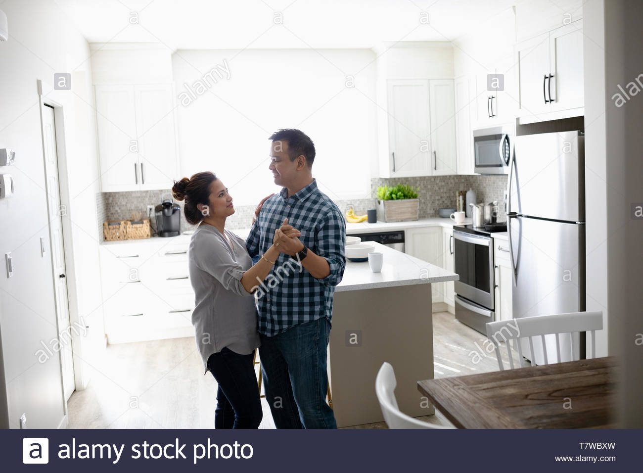 Affectionate couple dancing in kitchen Stock Photo