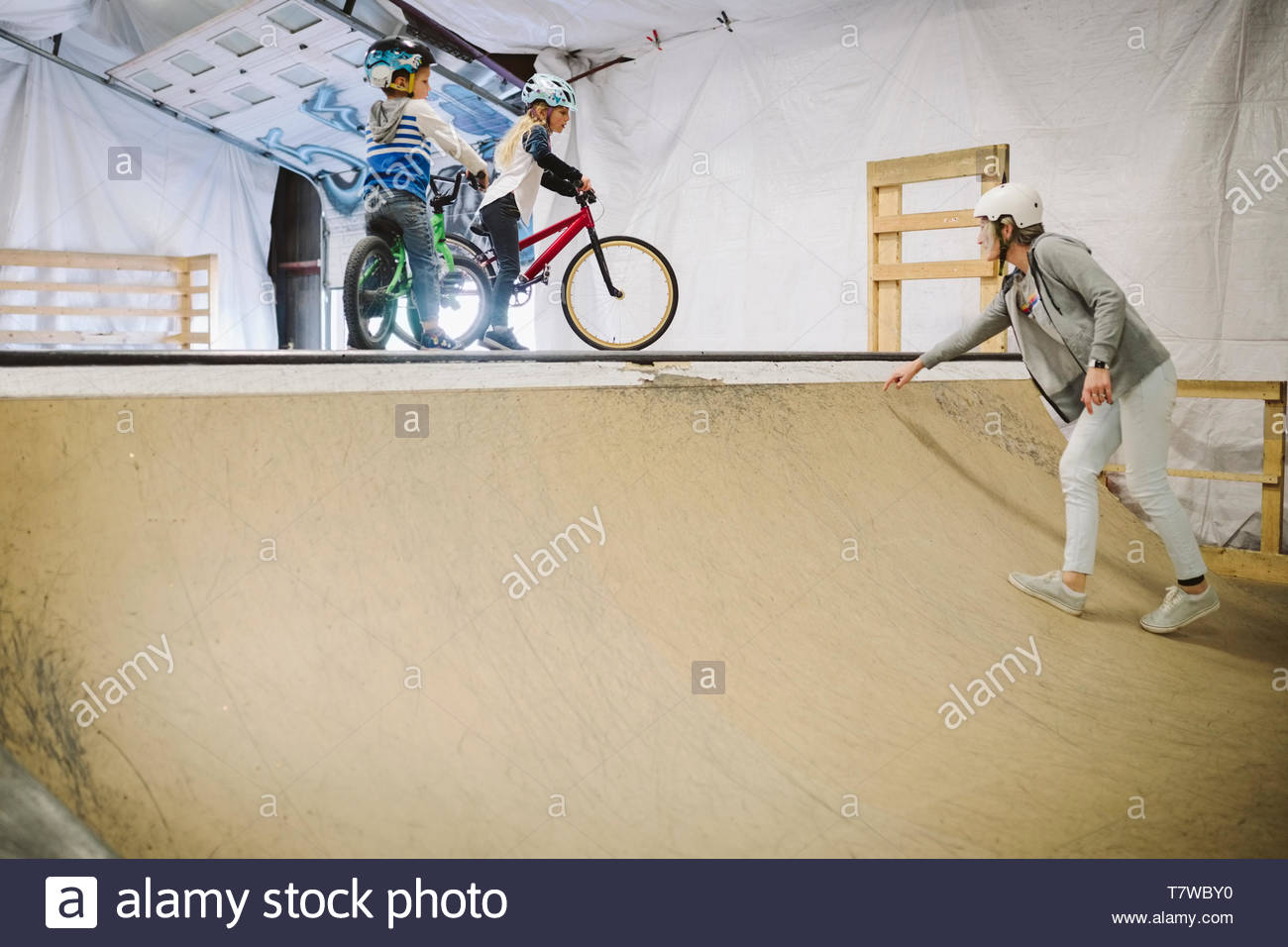 Mother guiding children on bmx bikes at ramp at indoor skate park - Stock Image