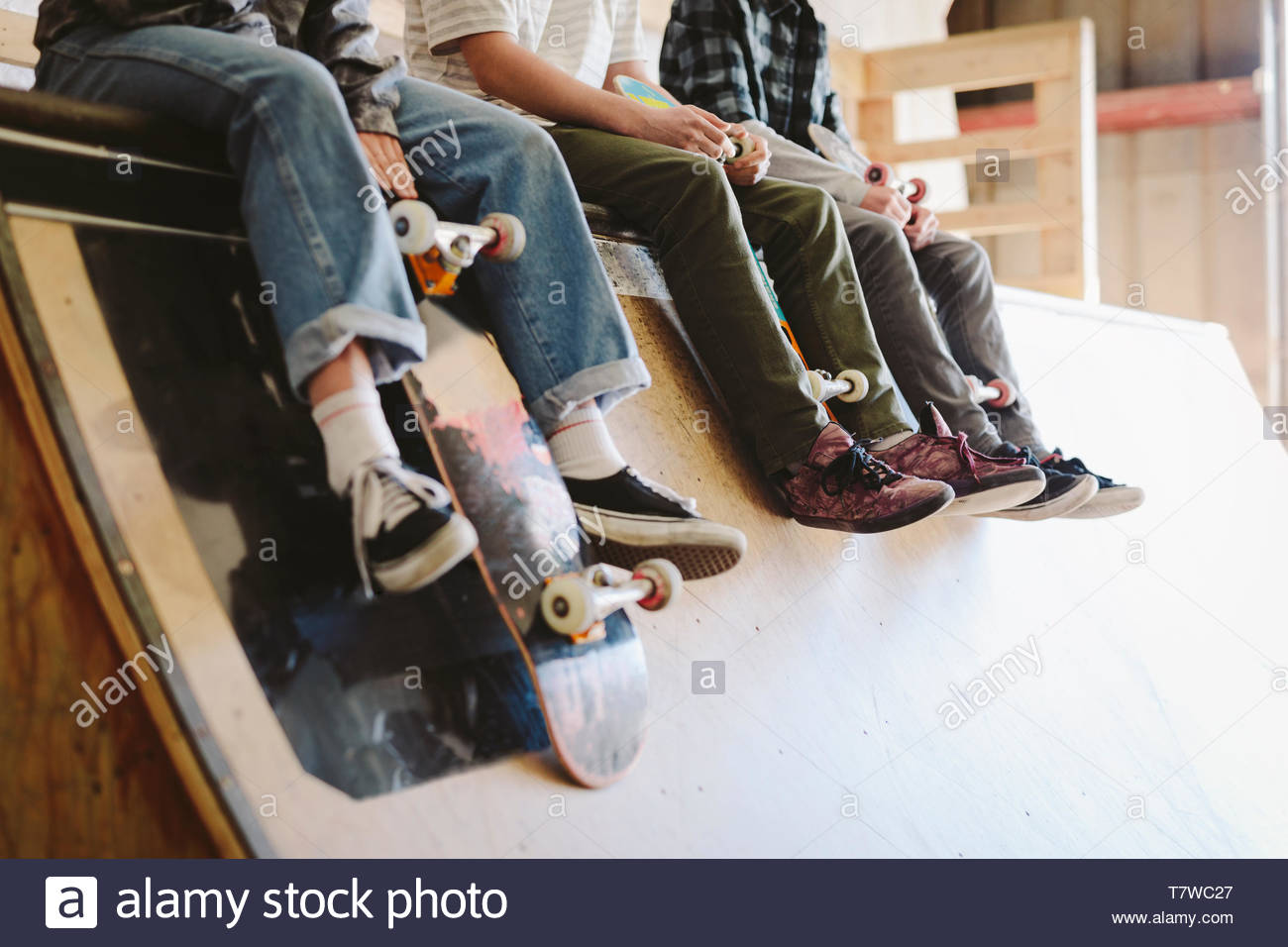 Friends hanging out, sitting at top of ramp at indoor skate park - Stock Image