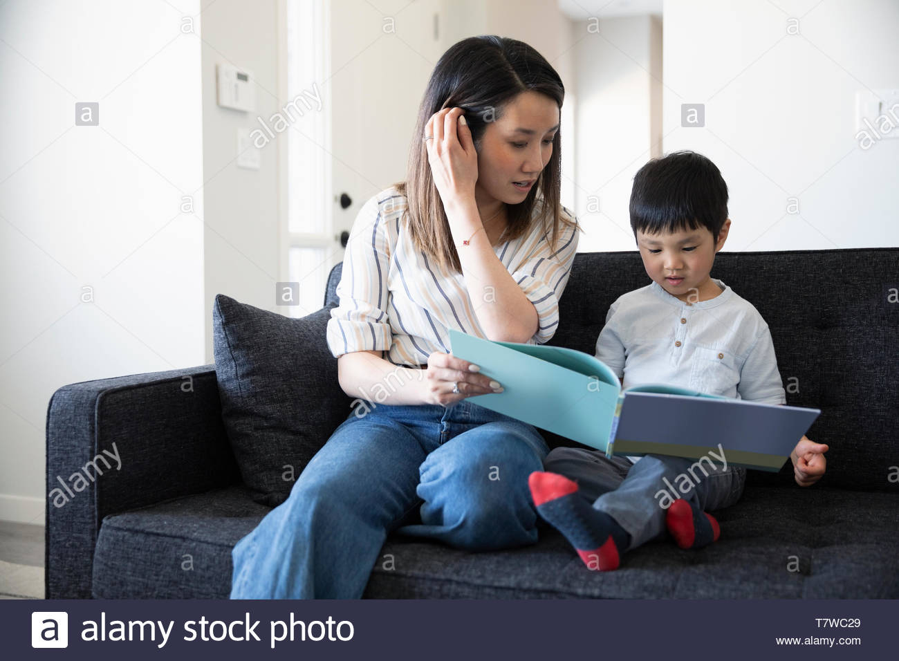 Mother and toddler son reading book on living room sofa Stock Photo