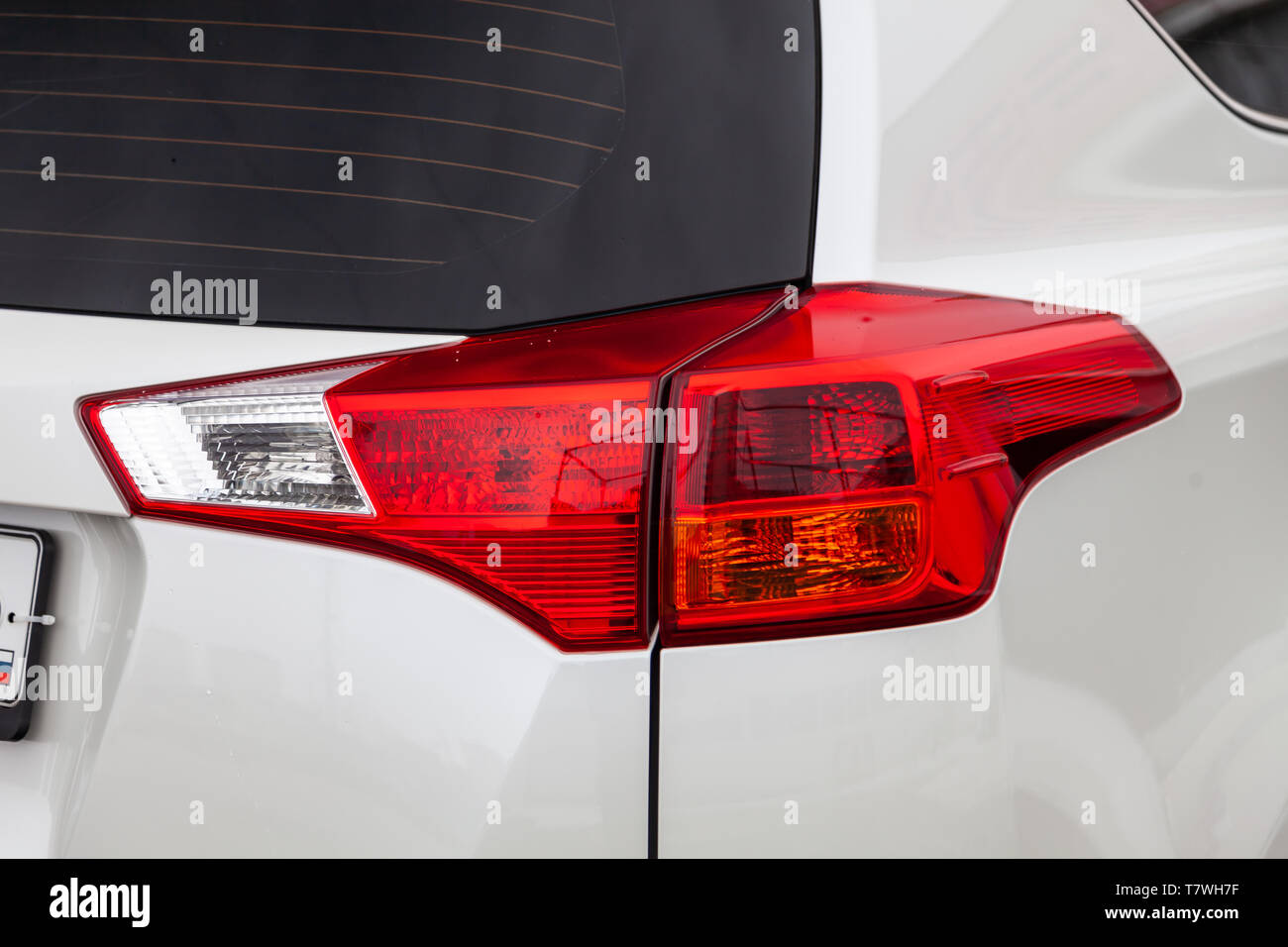 Close-up on the rear brake light of red color on a white car in the back of a suv after cleaning, polishing and detailing in the vehicle repair worksh - Stock Image