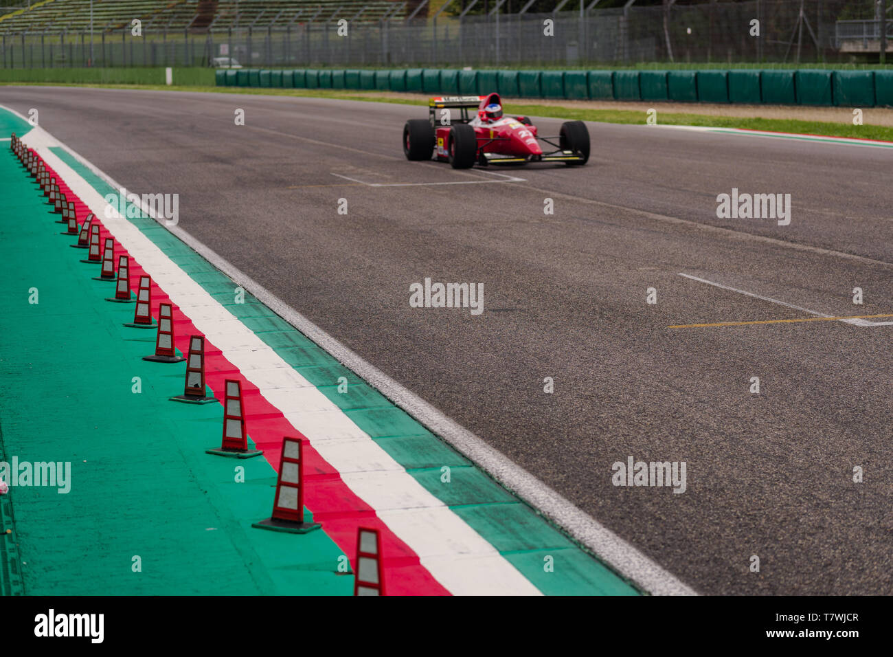 vintage ferrari is exiting from th the last corner to pass on the main straight at the full throttle Stock Photo