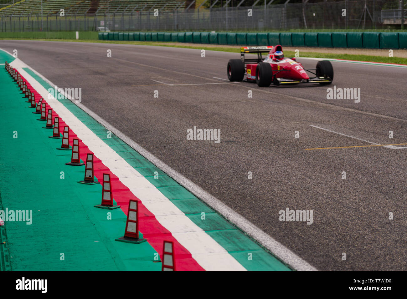 Vintage Ferrari is flying on the main straight of a race track Stock Photo