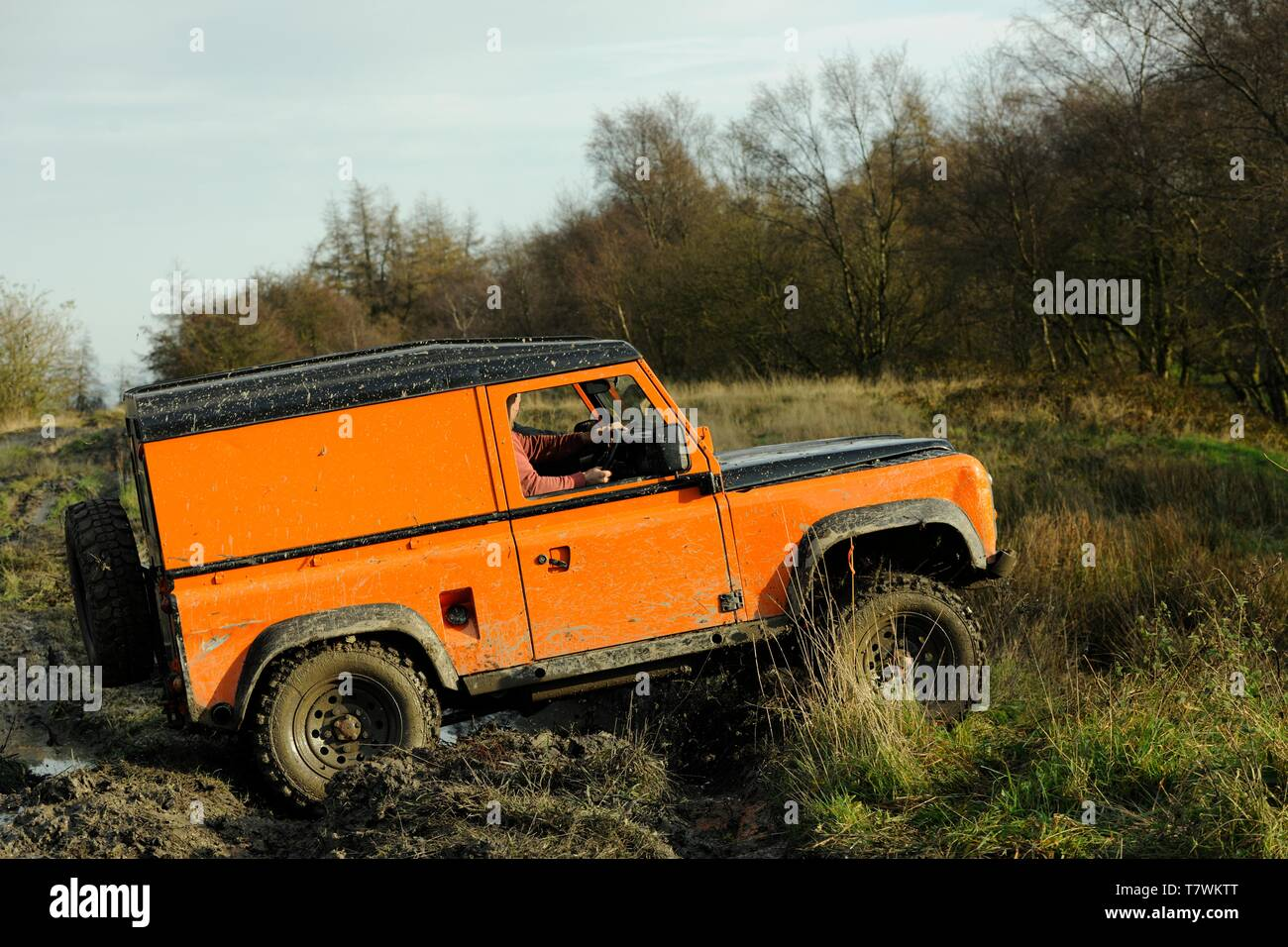 Off-road Landrover tackles a muddy trial course on a Winter's day in the Peak District, Derbyshire - Stock Image