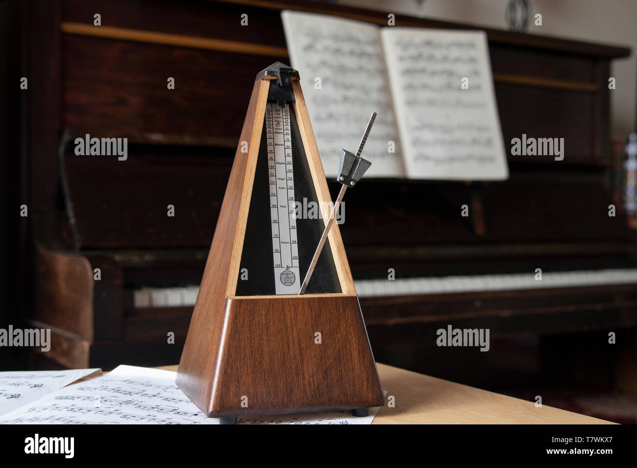 Old style Paquet wooden pyramid metronome standing on bundle of sheet music, in front of an open piano. - Stock Image