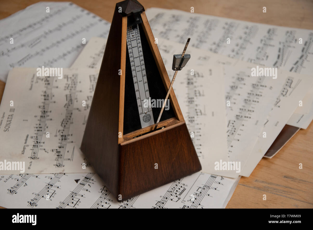 Old style Paquet wooden pyramid metronome standing on bundle of sheet music - Stock Image