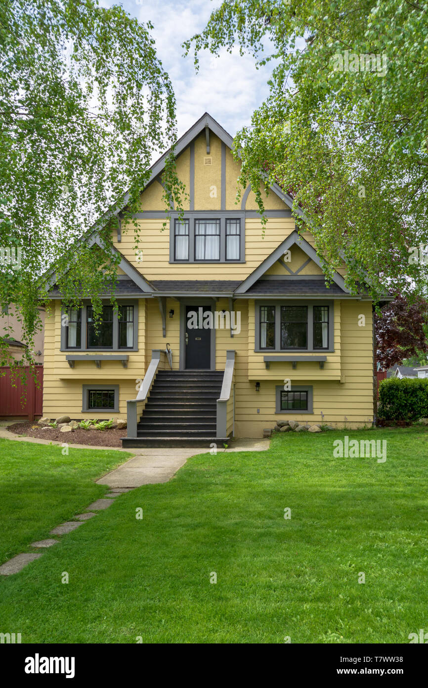 Yellow big old family house with spacios front yard. - Stock Image