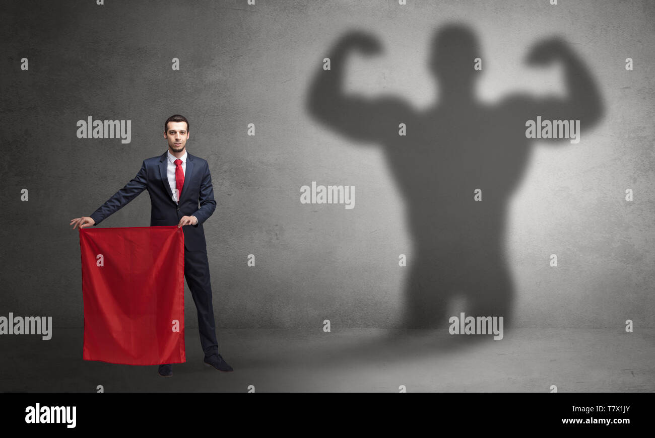 Businessman standing with red cloth on his hand and strong hero shadow on the background  - Stock Image