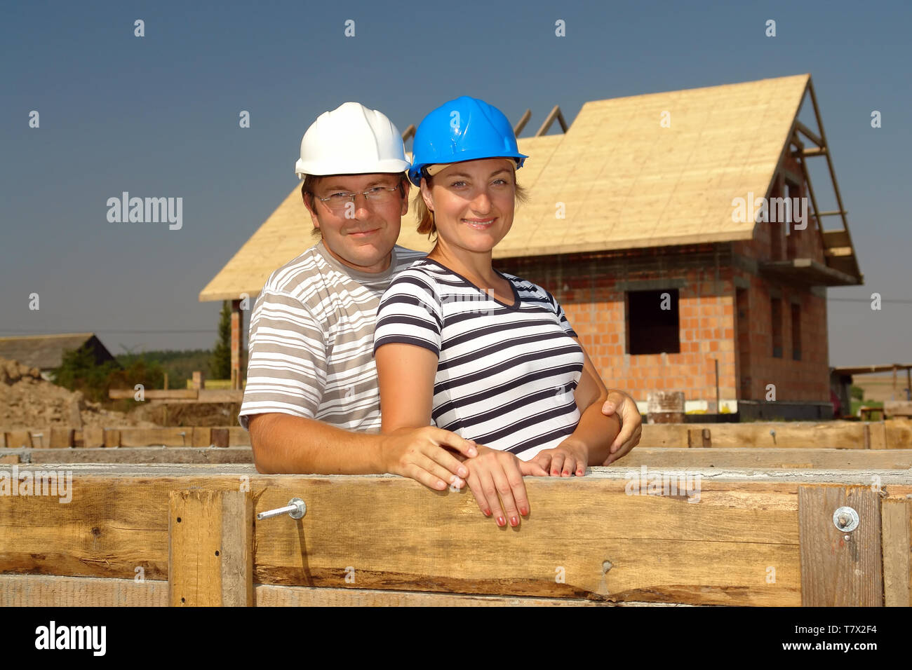 Couple wearing hard hats posing over unfinished house - Stock Image