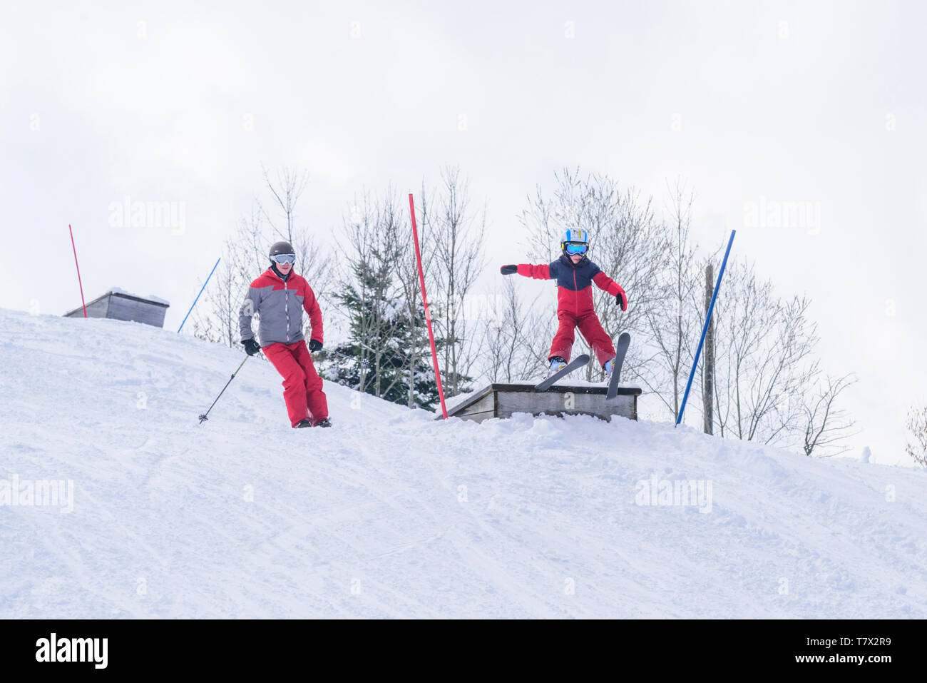 Little boy has a lot of fun on alpine skis while jumping over a ramp Stock Photo