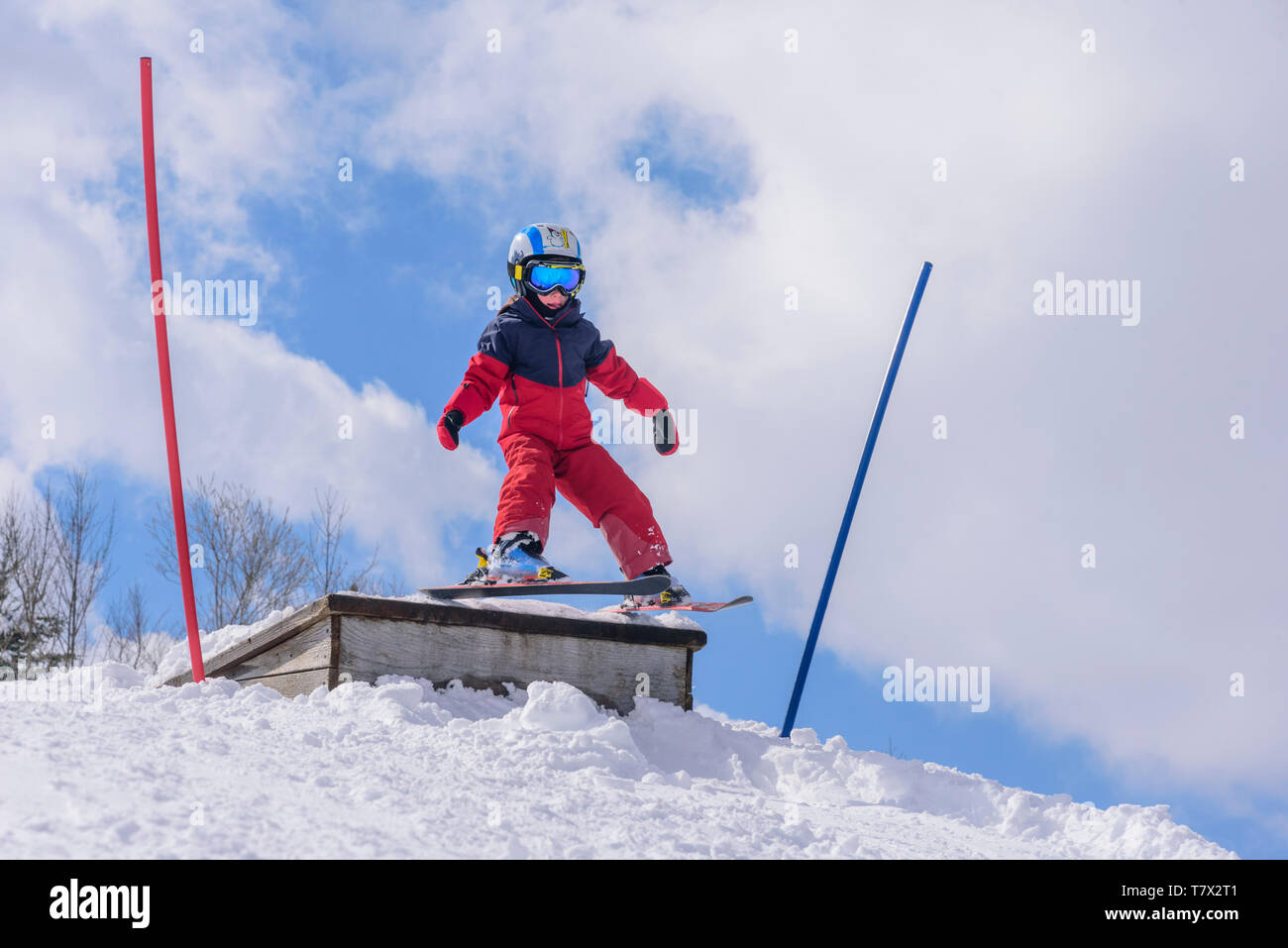 brave young boy jumping courageous from a wooden ramp - Stock Image