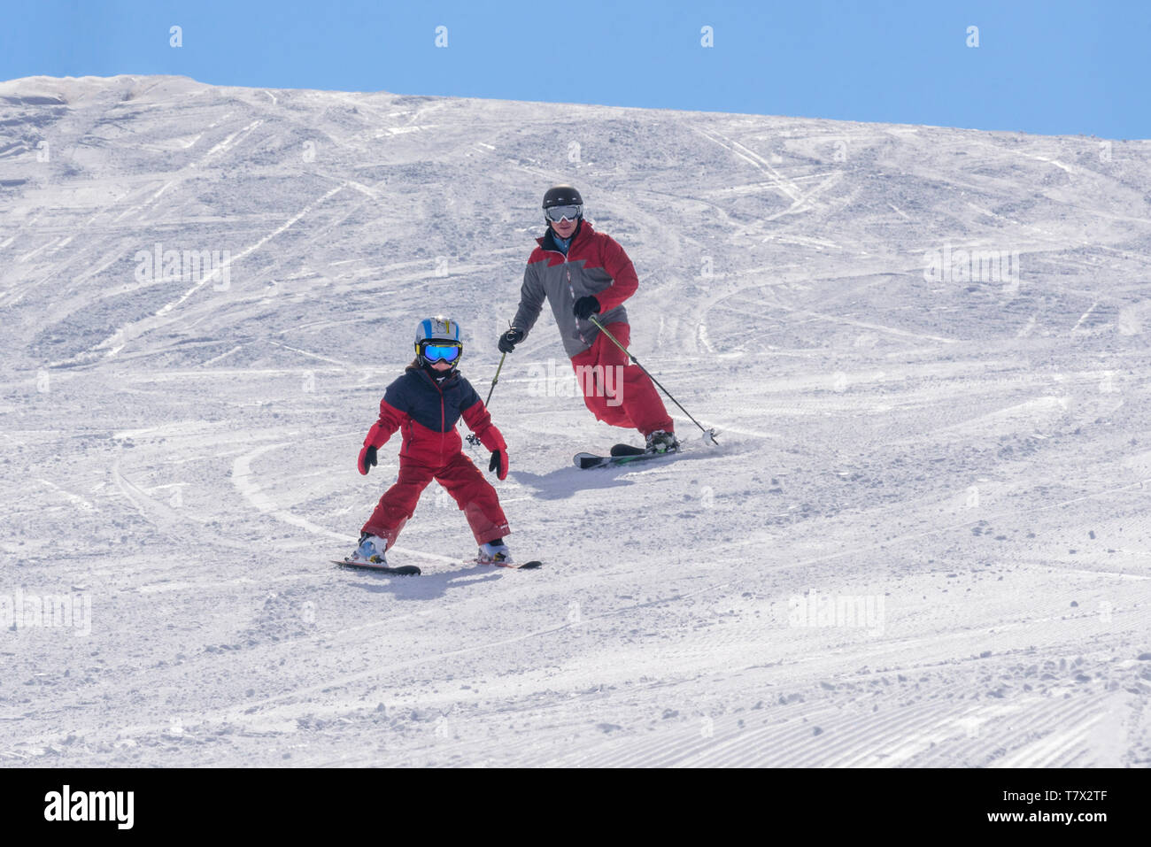 Young boy skiing with his father on good prepared slope Stock Photo