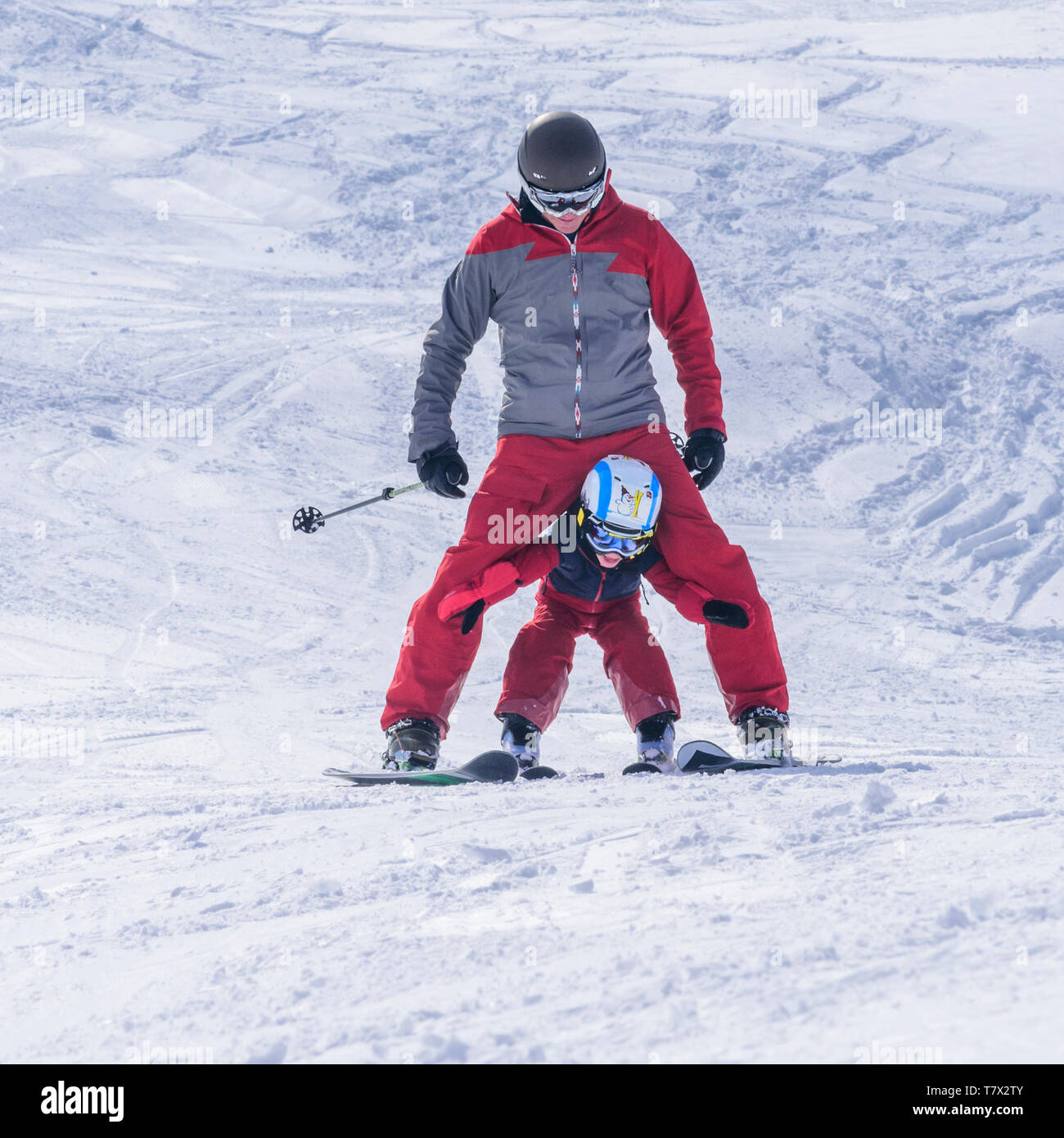 Young boy skiing with his father on good prepared slope - Stock Image