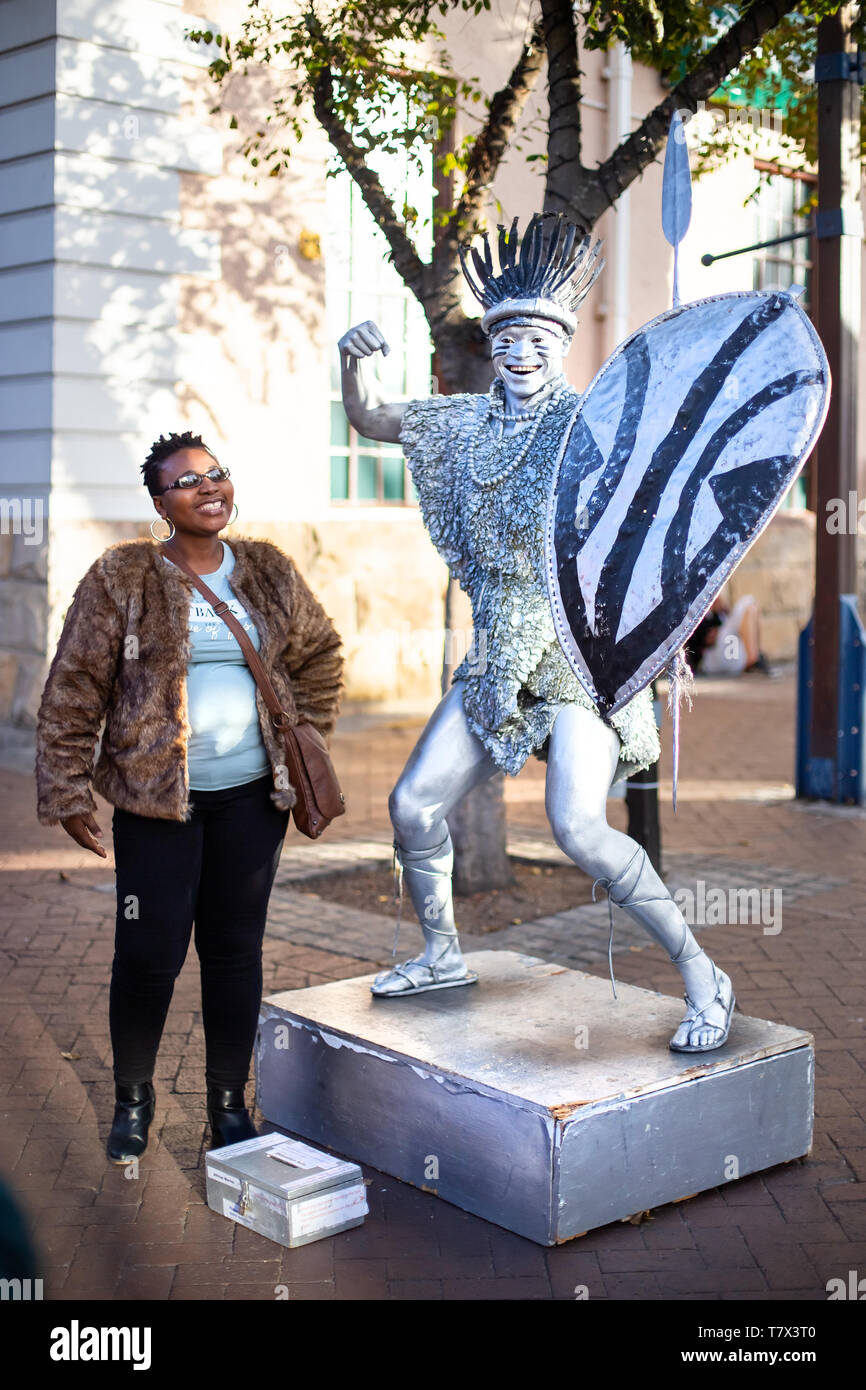Cape Town, South Africa, 12th April - 2019: Street performer performing for member of the public that is looking on. - Stock Image