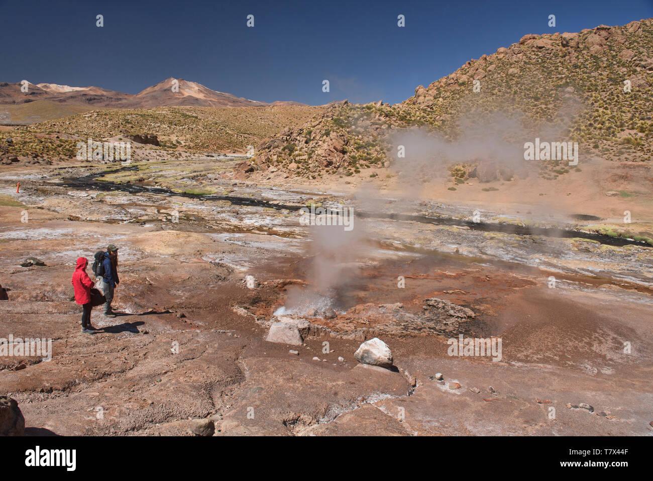 Watching a geyser erupt along the Rio Blanco, El Tatio, San Pedro de Atacama, Chile - Stock Image