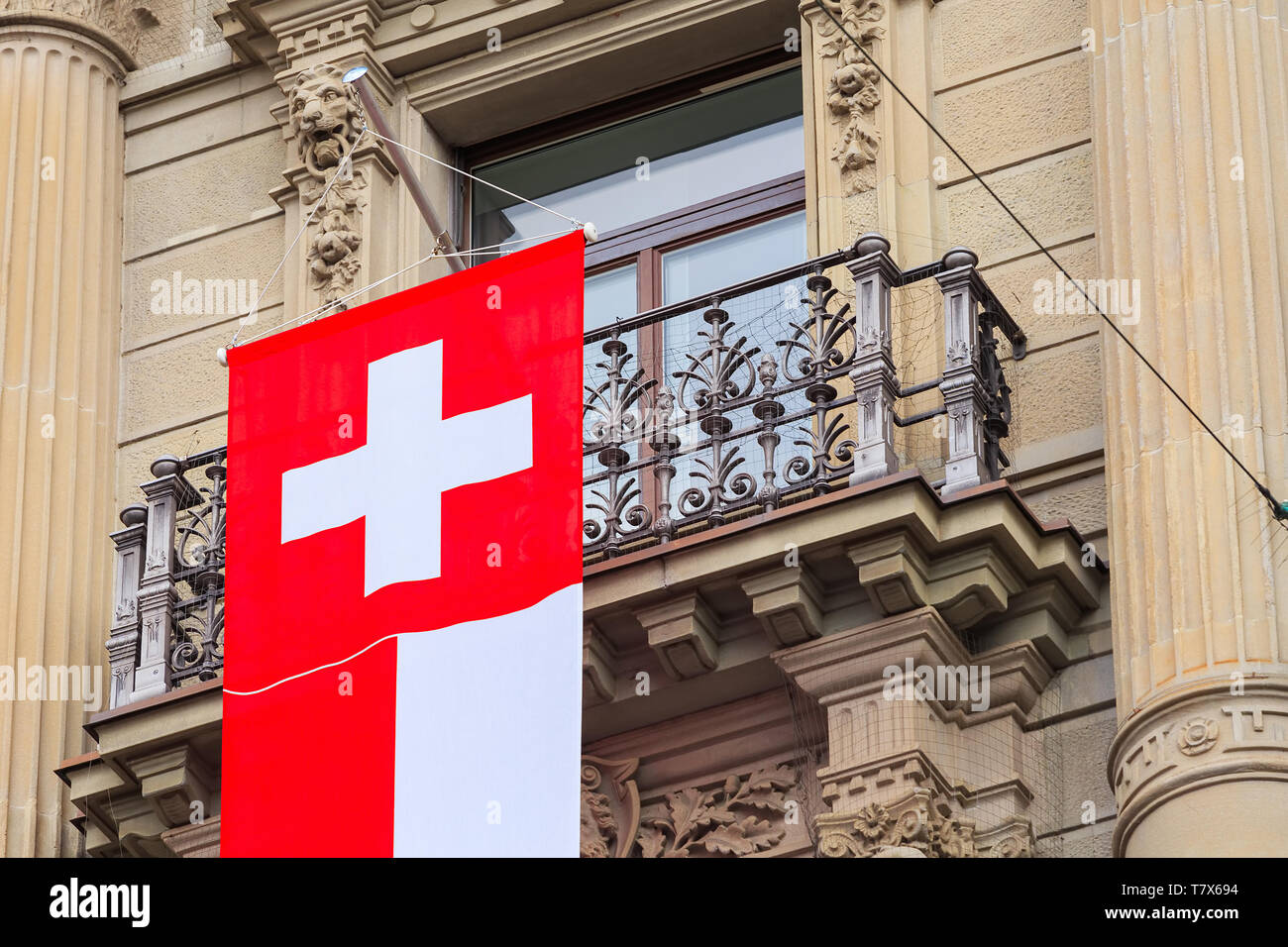 Zurich, Switzerland - August 1, 2016: a balcony of the Credit Suisse building at Paradeplatz square in the city of Zurich decorated with a flag of Swi - Stock Image