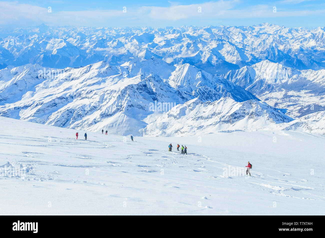 A group of freeriders skiing on the wide glacier area of Monte Rosa with fantastic view to the alps Stock Photo