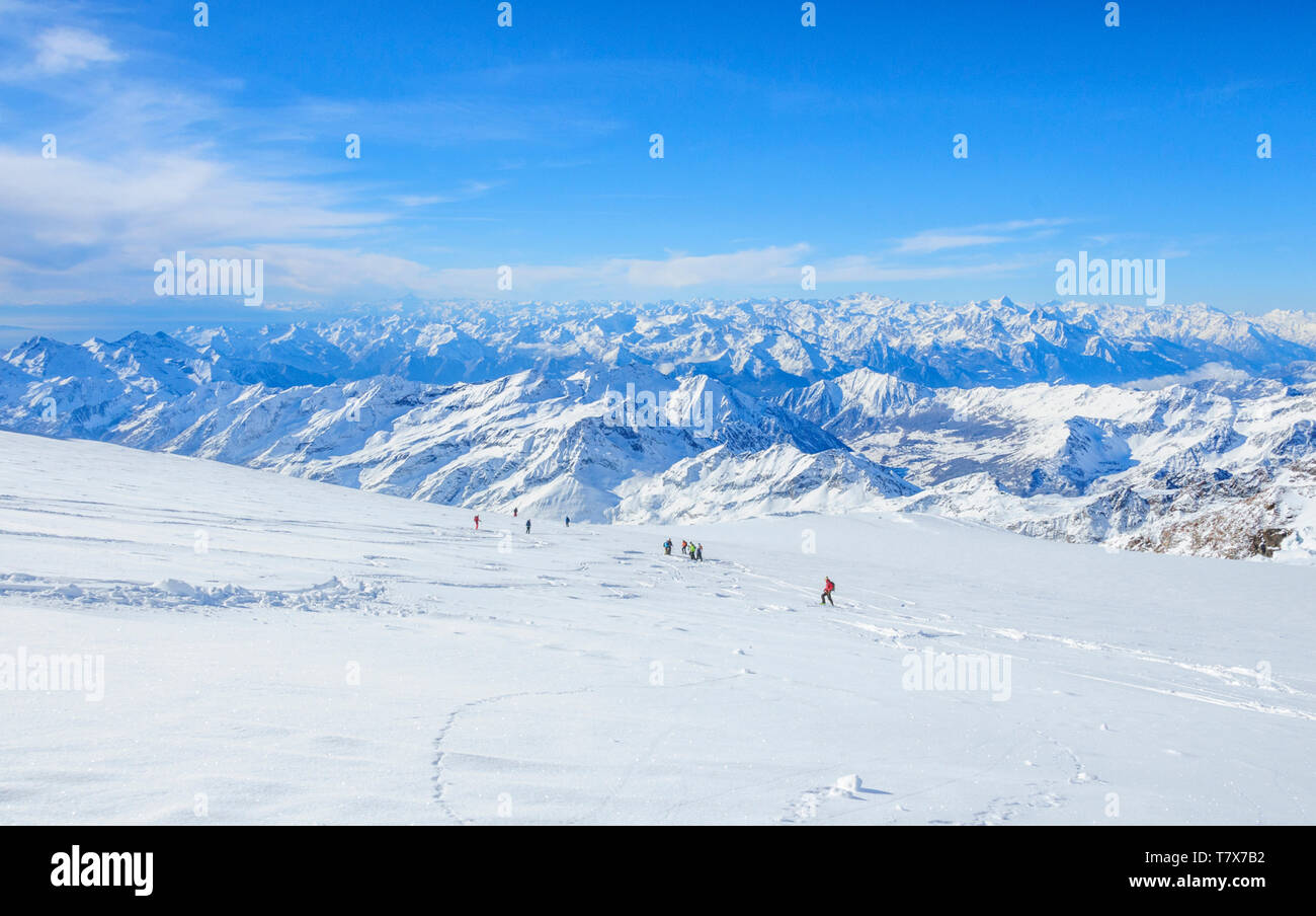 A group of freeriders skiing on the wide glacier area of Monte Rosa with fantastic view to the alps - Stock Image