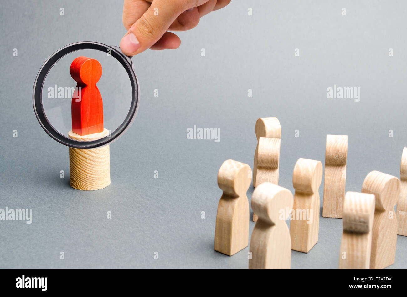 Magnifying glass is looking at the red man stands on the podium and appeals to the crowd of people. Agitation, appeal and appeal to the crowd. Leader  - Stock Image