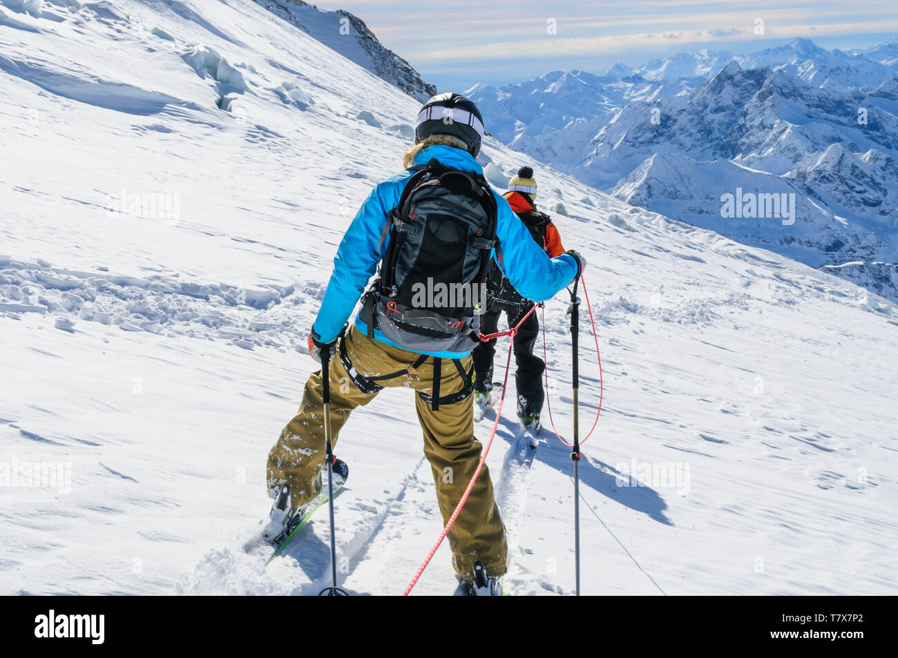 Rope team skiing with a mountain guide in dangerous glacier area - Stock Image