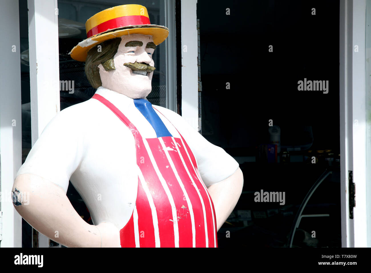 Lyme Regis, Dorset - Antique, life size, jolly butcher statue standing outside butchers shop in the daytime Stock Photo