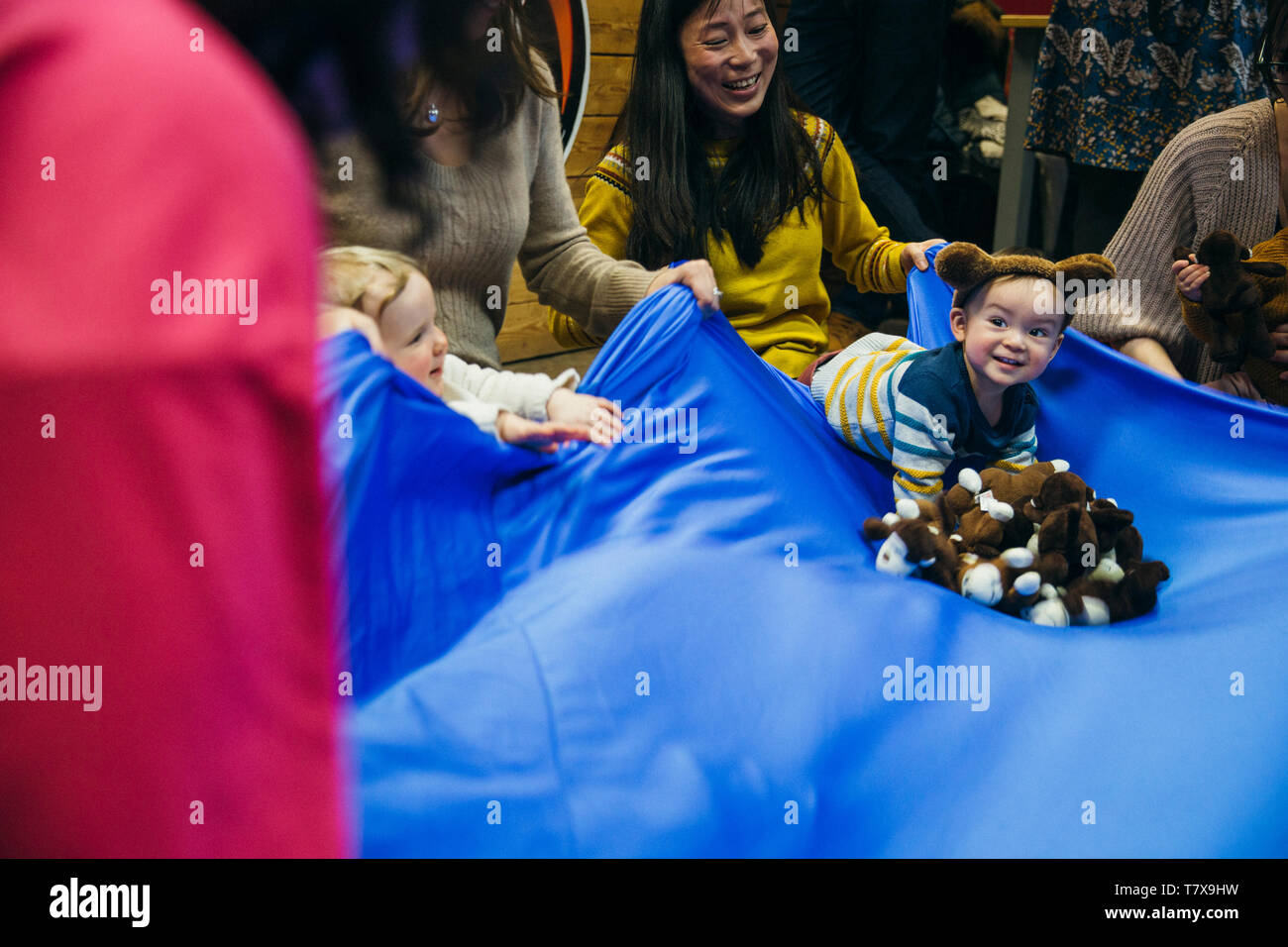 Little boy is having fun at playgroup woth his mother and other families. - Stock Image