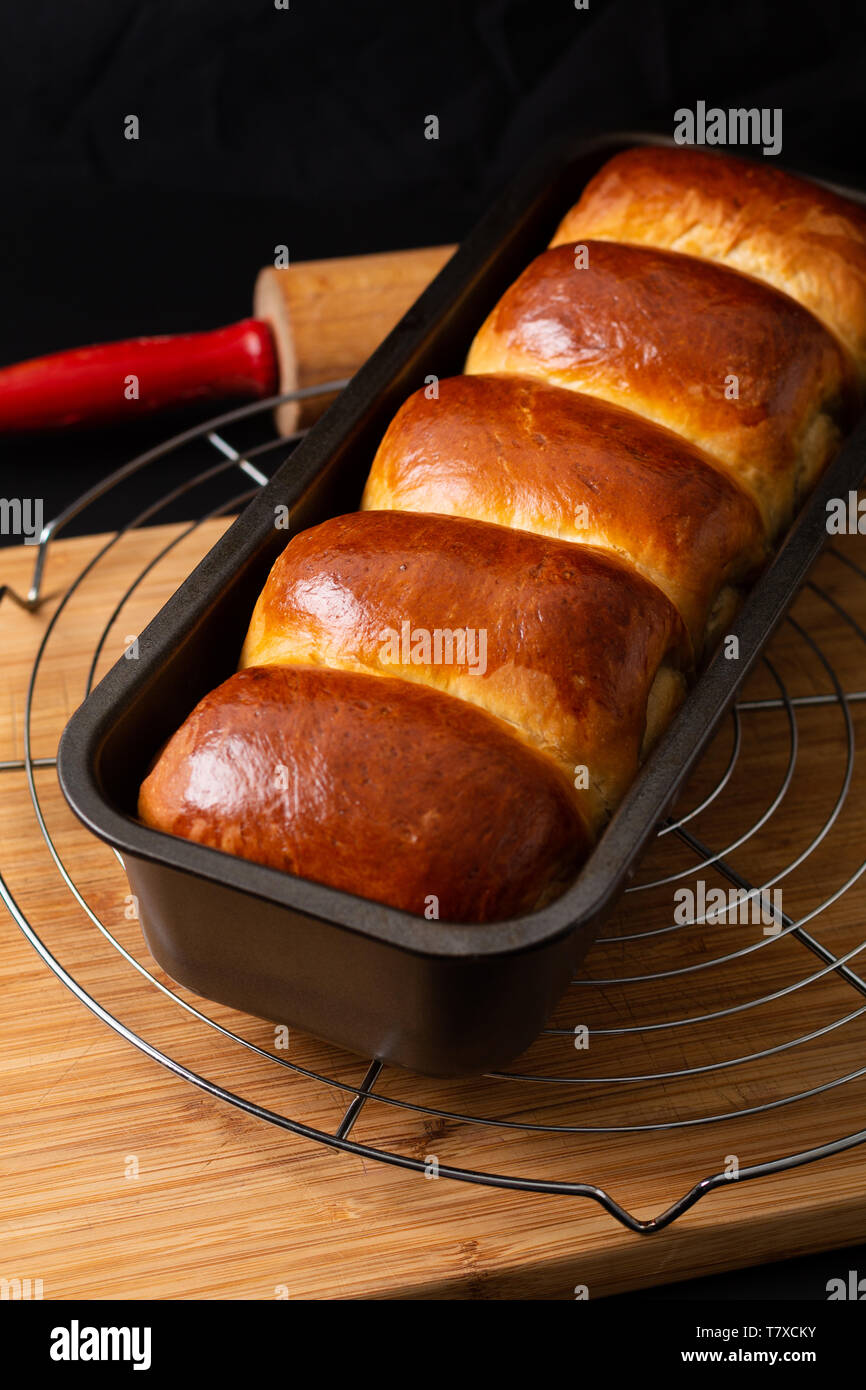 Food Baking concept Fresh baked organic homemade soft milk loaf bread in loaf pan on wooden board with copy space Stock Photo