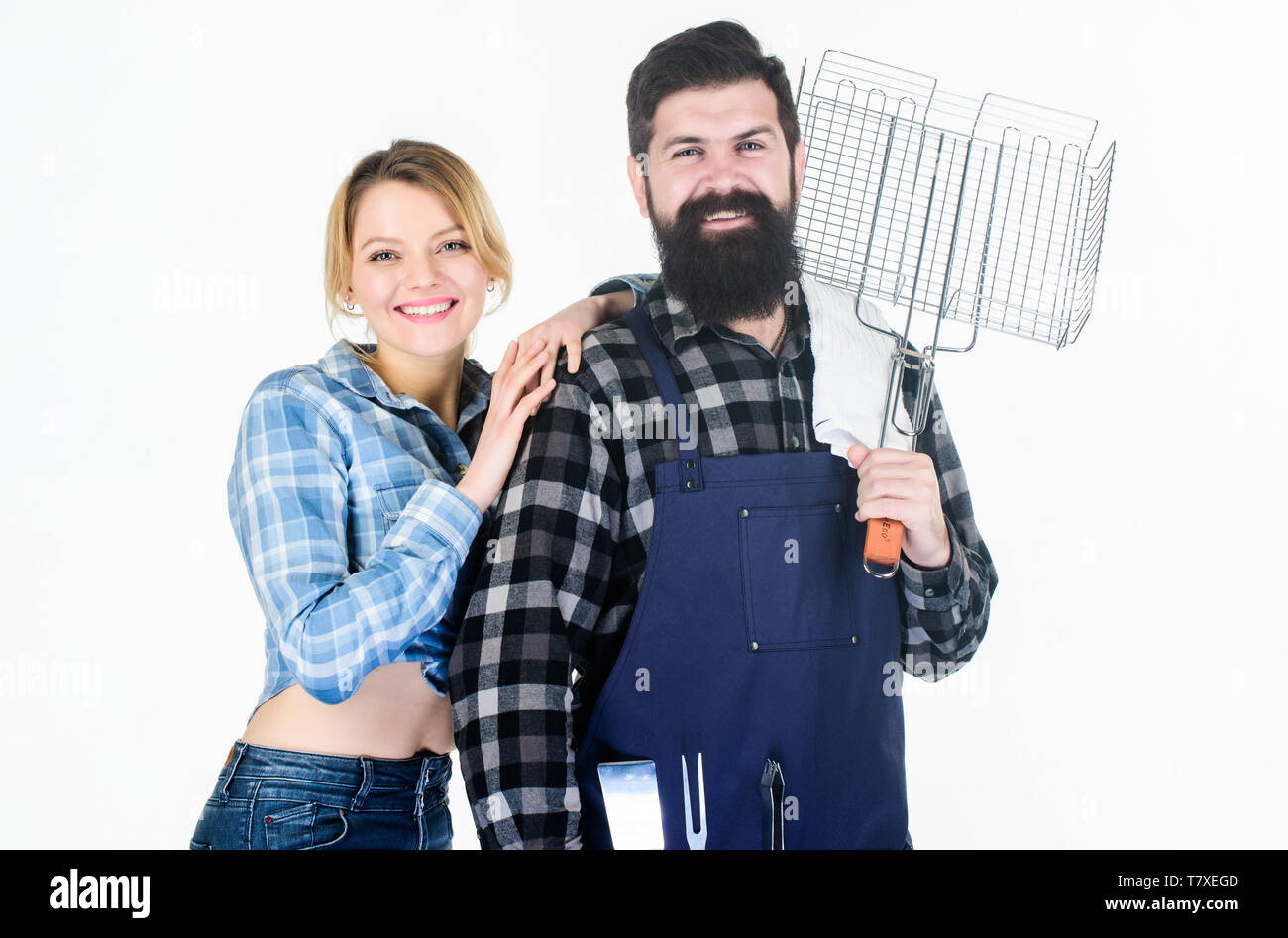 Happy loving couple. Man bearded hipster and girl. Preparation and culinary. Family weekend. Picnic barbecue. food cooking recipe. Couple in love hold kitchen utensils. Tools for roasting meat. - Stock Image