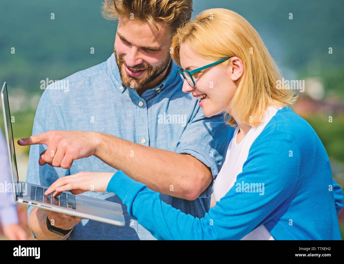 Couple working laptop outdoor sunny day, nature background. Man and girl interested information screen notebook. Mobile internet concept. Internet gives possibility to work from everywhere in world. - Stock Image