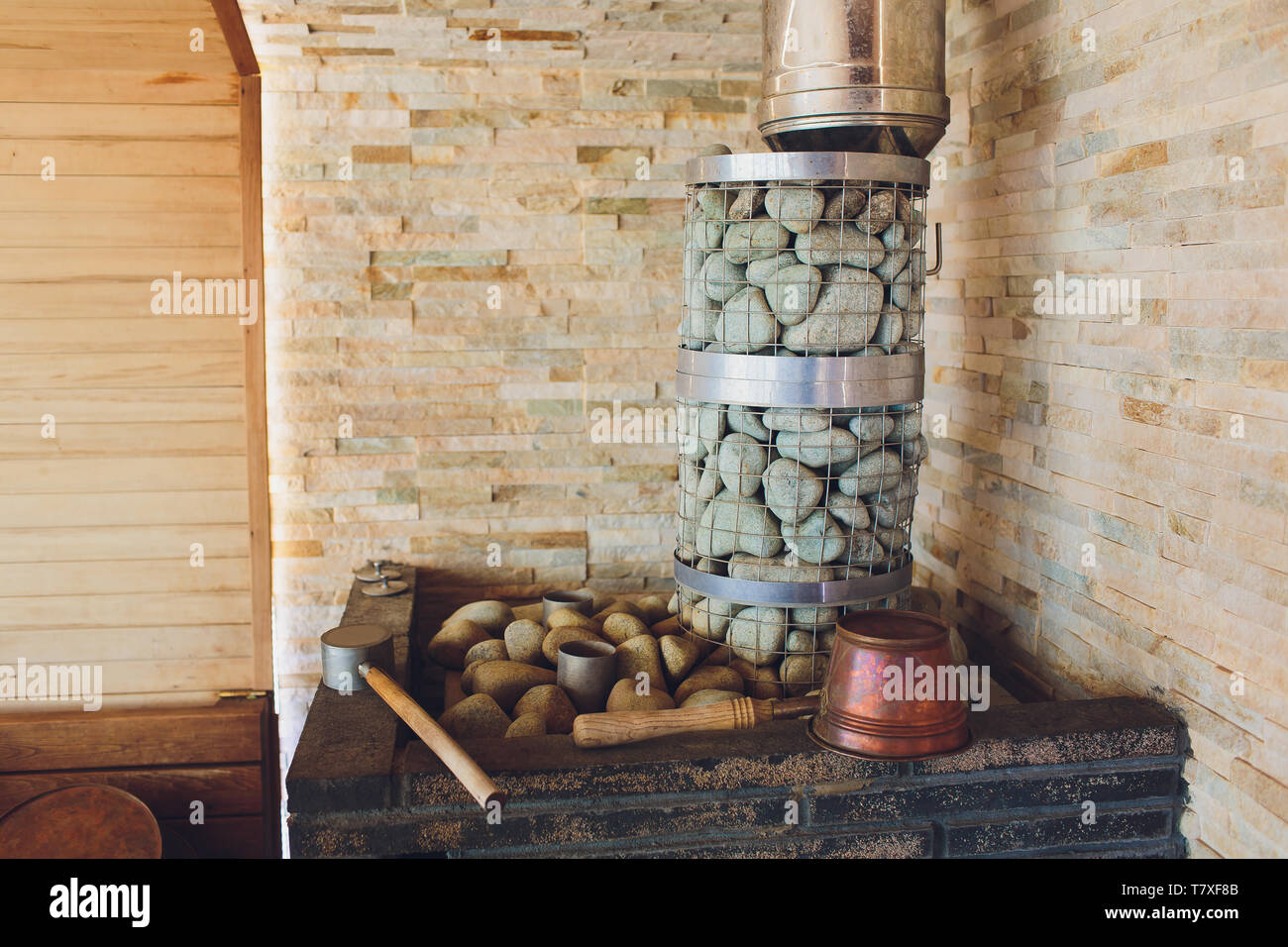 Interior of traditional finnish sauna with stones on the stove and wooden walls, indoors close-up - Stock Image
