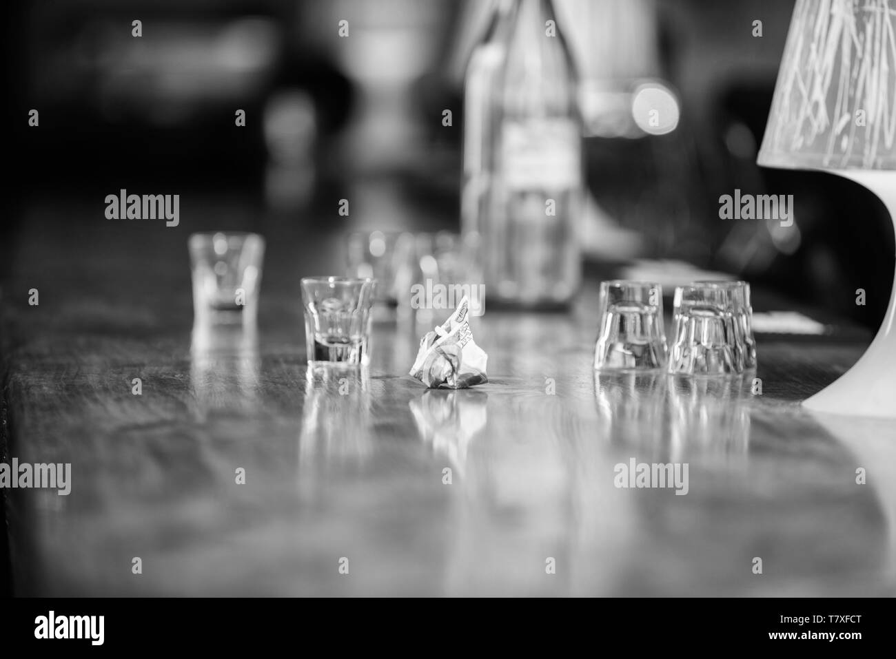 Purchase and payment. Cash money concept. Leave tips for bartender. Tip given to waiter. Crumpled money cash at bar counter. Empty glasses and bottle on table. Cash payment. Ordering drinks in bar. - Stock Image