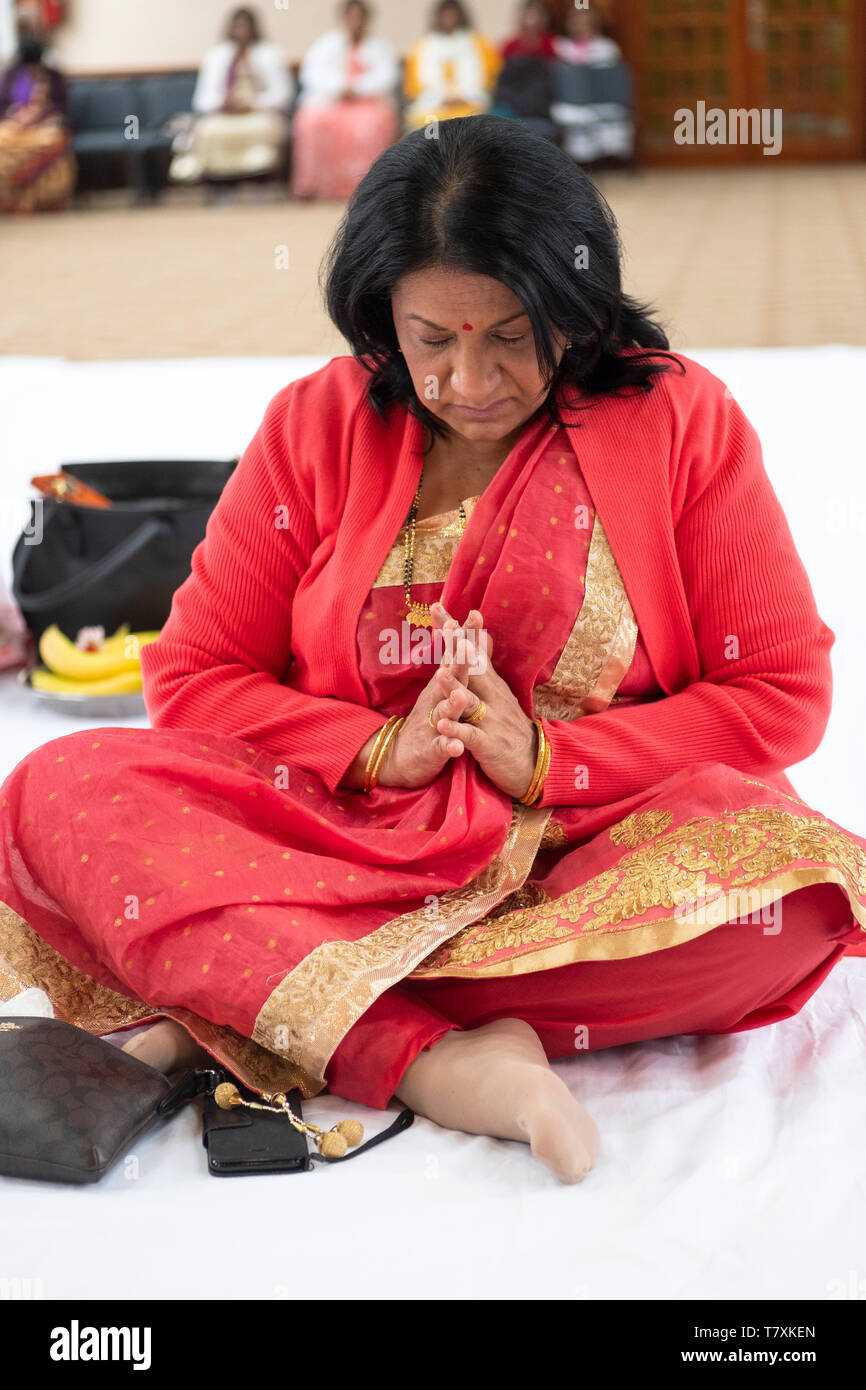 An attractive middle aged  Hindu woman in a beautiful sari with her hands clasped in a temple in Jamaica, Queens, New York City. Stock Photo