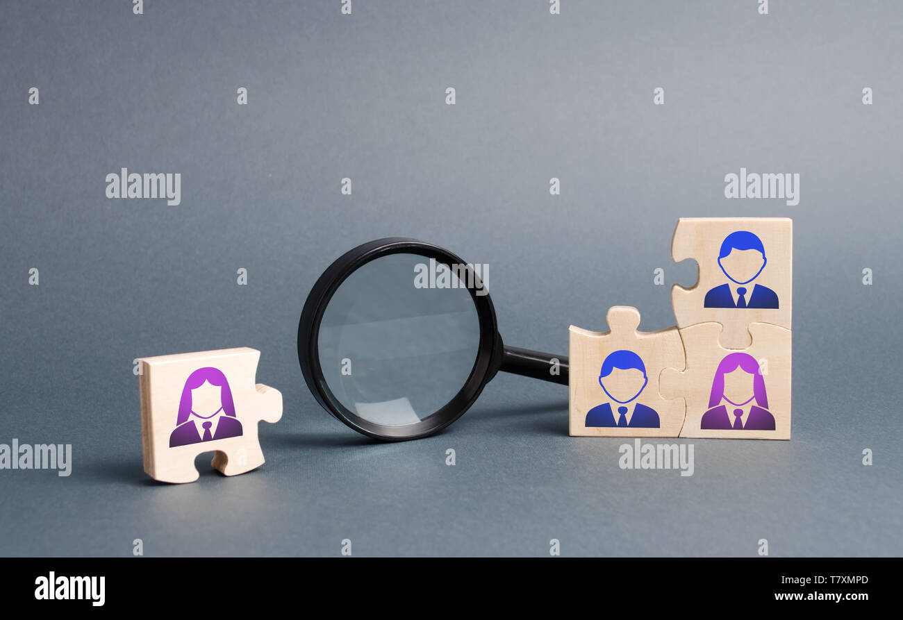 Unsorted team puzzle and magnifying glass. Search, recruitment staff, hiring leader. Lack of specialists in the labor market. Creating an efficient an - Stock Image